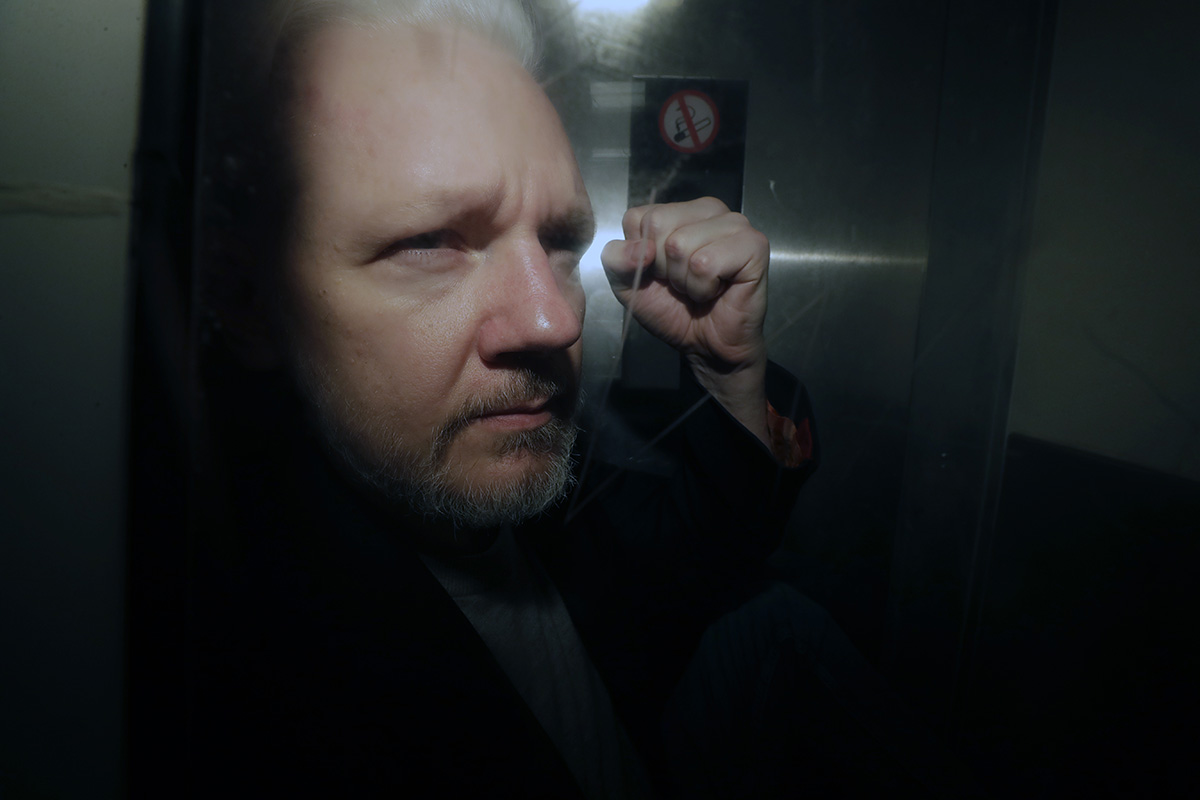 In this May 1, 2019, file photo, WikiLeaks founder Julian Assange puts his fist up as he is taken from court in London. (Matt Dunham/AP)