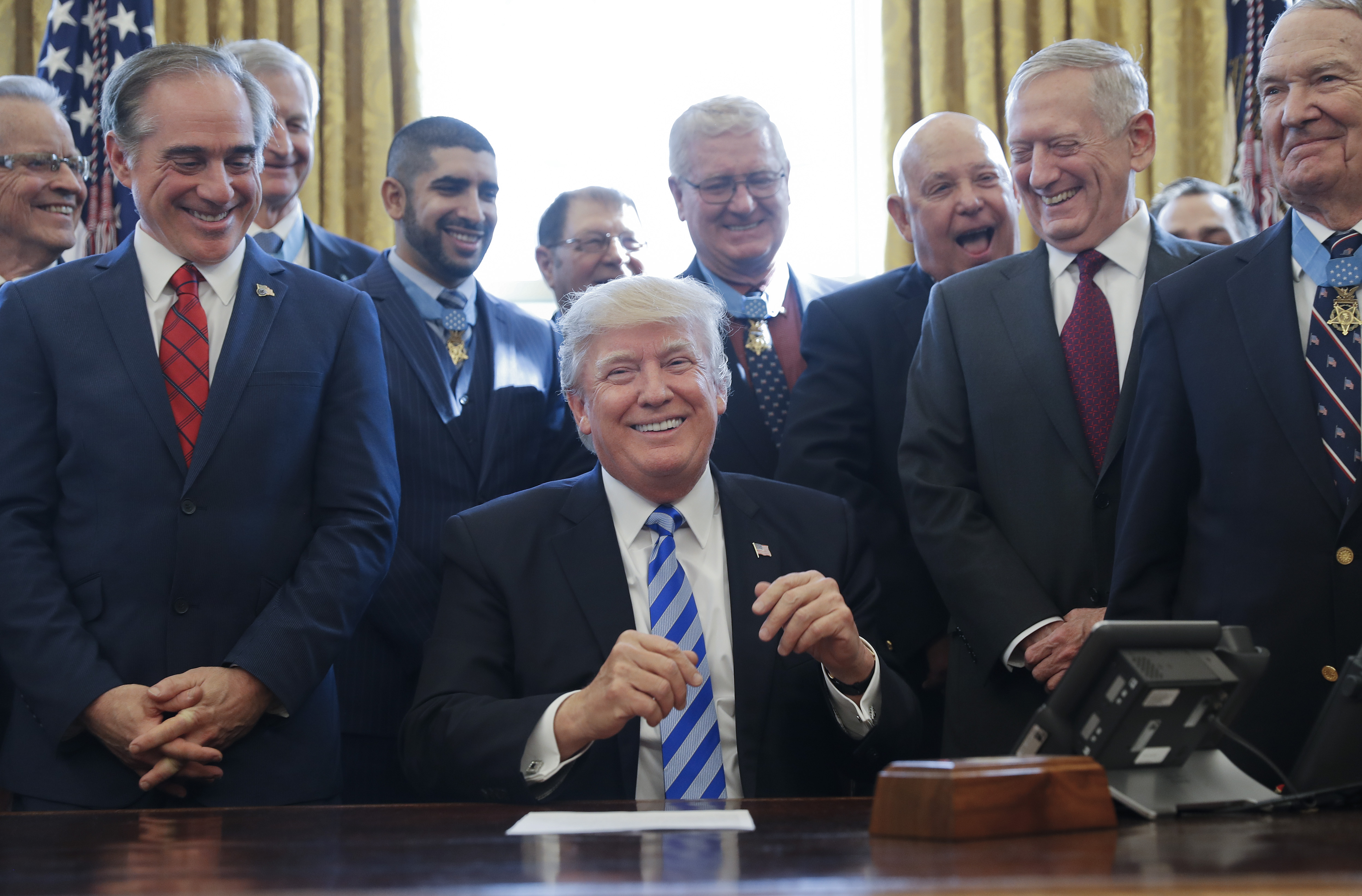 President Donald Trump smiles during a ceremony with Medal of Honor recipients at the White House on March 24, 2017. At left is then-Secretary of Veterans Affairs David Shulkin, whose new book details chaos and confusion within the administration before his firing in 2017. (Pablo Martinez Monsivais/AP)
