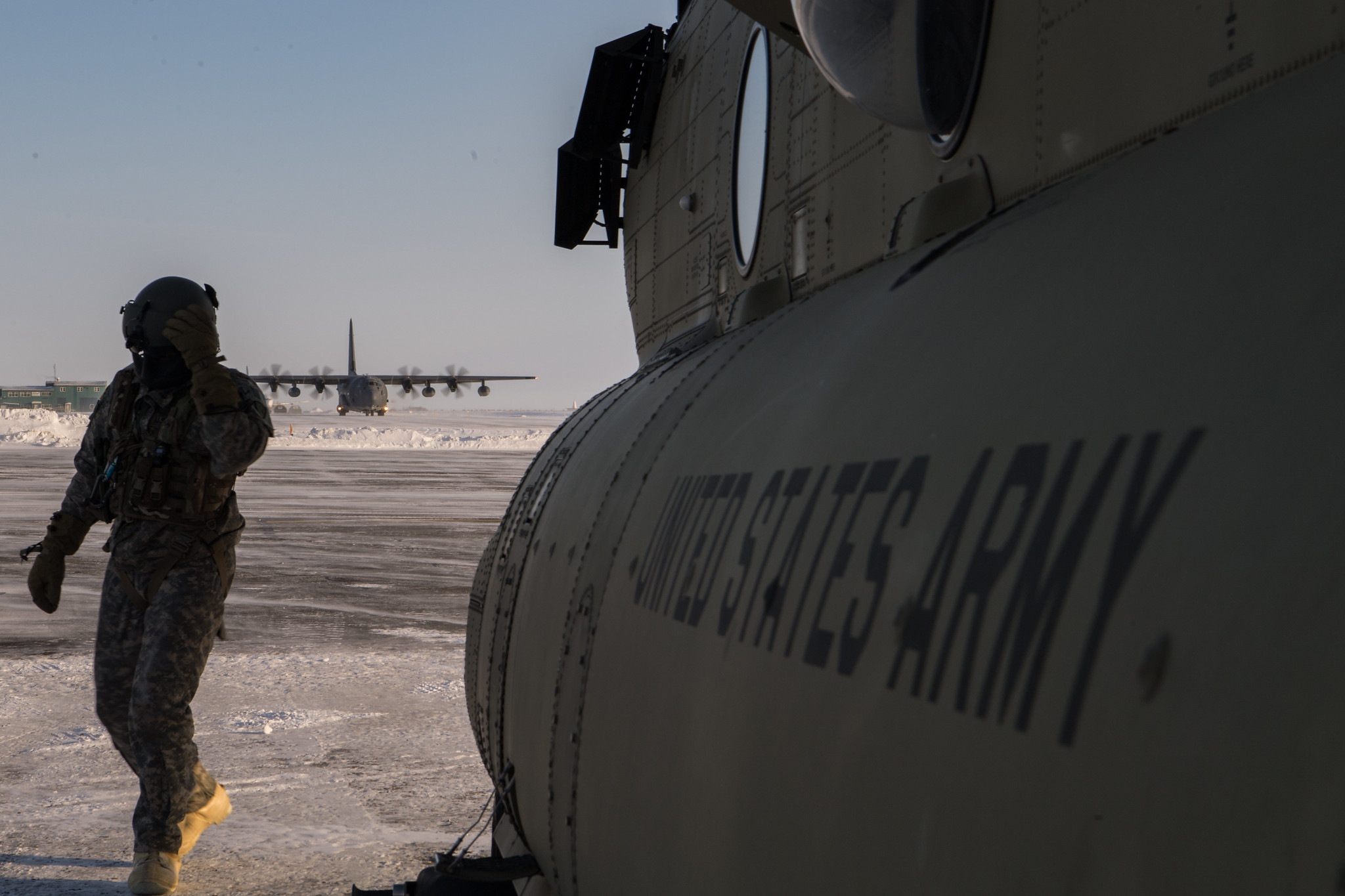 Army Sgt. Lucas Bartel exits the flightline after the completion of a tail-to-tail exchange of cargo and personnel from a CH-47 Chinook helicopter and an HC-130J Combat King II near Deadhorse, Alaska, in support of exercise Arctic Eagle 2020, Feb. 28. (Tech. Sgt. Amy Picard/Air Force)