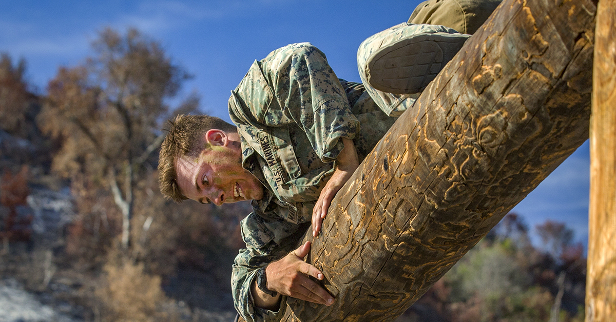 Marine Corps Lance Cpl. John Marino, a machine gunner with 1st Marine Regiment, climbs over a log during the obstacle course portion of the 1st Marine Division (MARDIV) Super Squad Competition at Marine Corps Base Camp Pendleton, California, Aug. 30, 2018. (Lance Cpl. Audrey M.C. Rampton/Marine Corps)