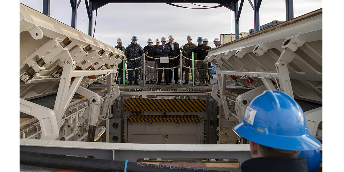 Secretary of the Navy Richard V. Spencer is briefed by the aircraft carrier Gerald R. Ford's skipper, Capt. John J. Cummings on the Upper Stage 1 advanced weapons elevator from atop Ford's flight deck.(Mass Communication Specialist 2nd Class Kiana A. Raines/Navy)