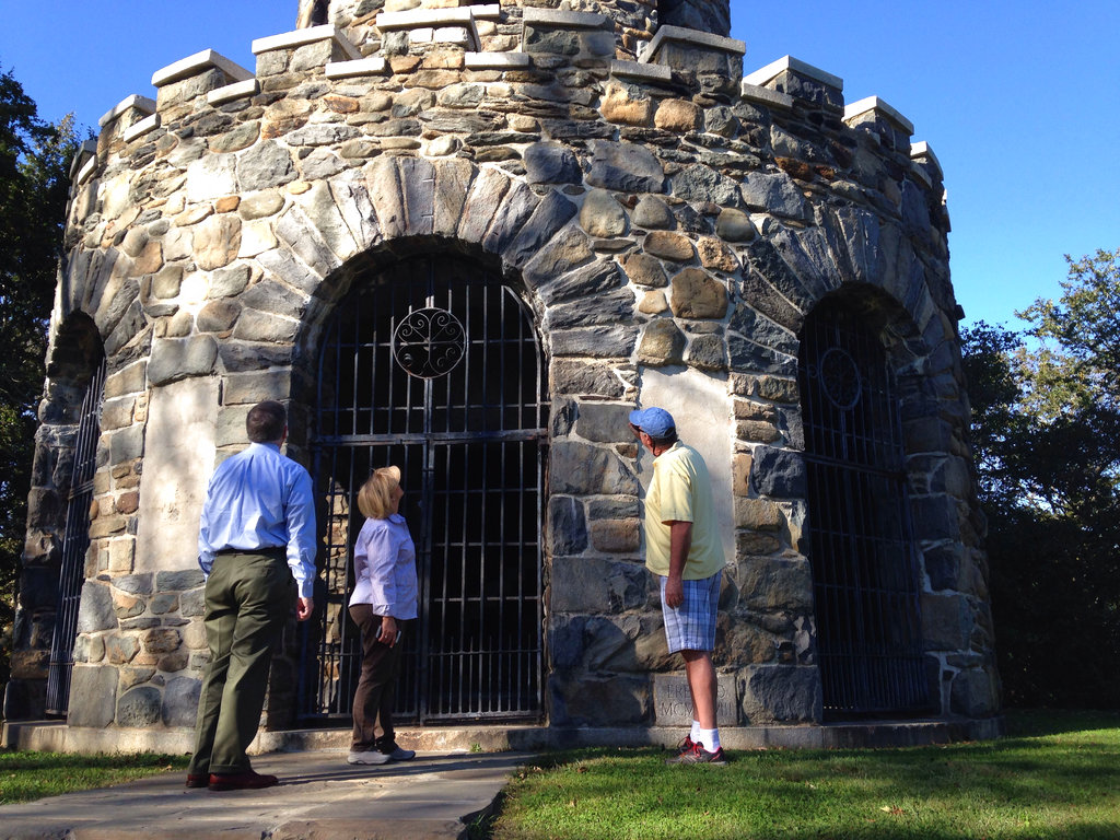 In this Friday, Sept. 29, 2017, photo, Jack Monahan, member of the U.S. World War I Centennial Commission, left, views a World War I memorial, which was vandalized about 40 years ago, with Bob Cornett, right, and Edith Fletcher, center, at Miantonomi Memorial Park Tower in Newport, R.I. The tower once featured bronze plaques with the names of WWI soldiers from the area who perished. The centennial of America's involvement in World War I has drawn attention to the state of disrepair of many monuments honoring soldiers, galvanizing efforts to fix them. (Jennifer McDermott/AP)