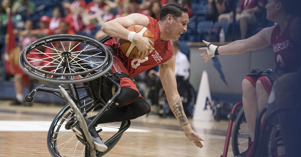 Marine Corps Staff Sgt. Jason Pacheco takes a spill as Navy defeats Marine Corps to win the wheelchair basketball bronze medal during the 2018 DoD Warrior Games.(Roger L. Wollenberg/DoD)
