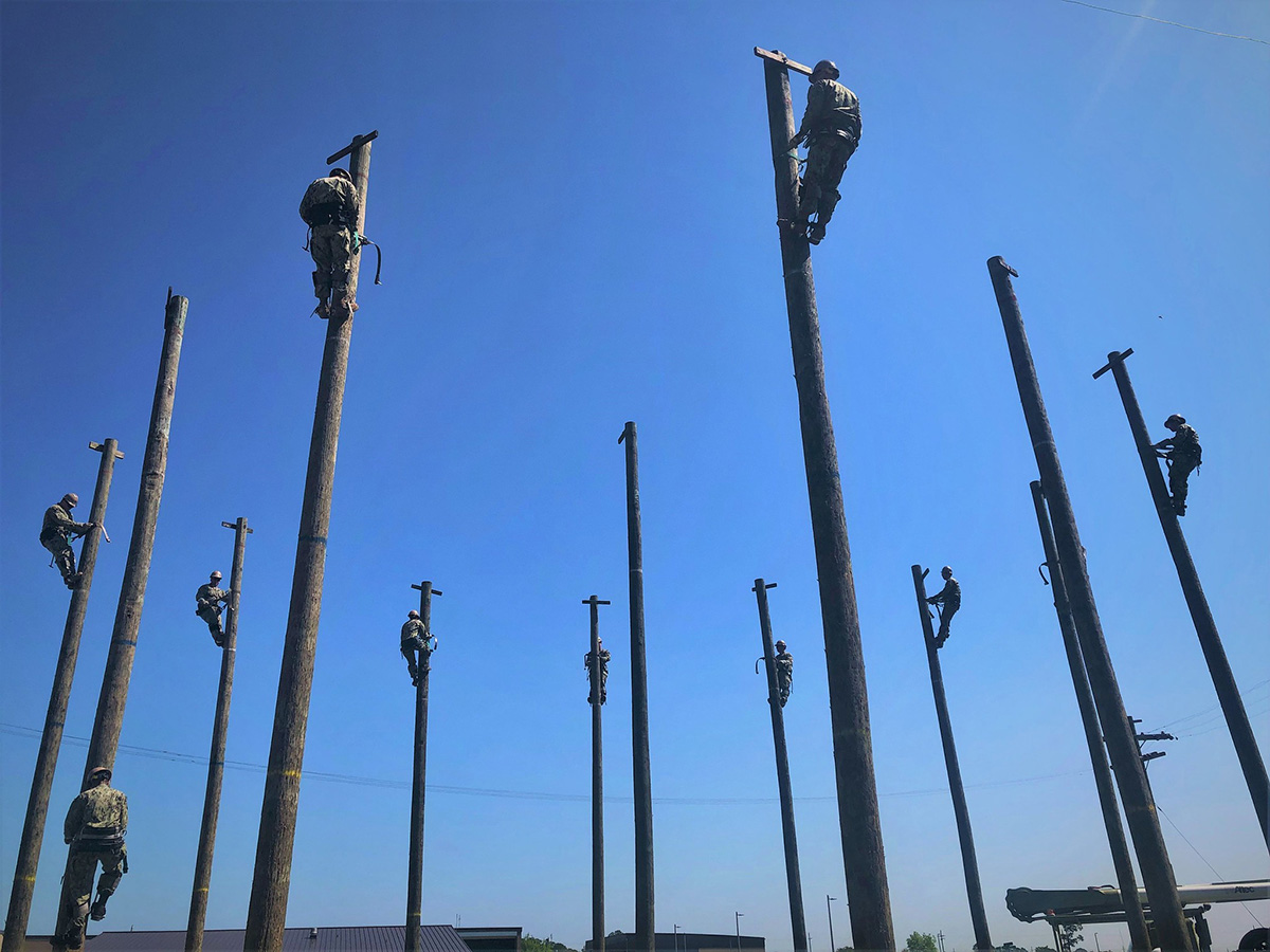 "Seabees attending Construction Electrician Core ""C"" School Pipeline training at Naval Construction Training Center Gulfport on May 20, 2019, advance their skills with wooden power pole utility work during a three-week power distribution systems and line vehicles course in Mississippi. (Chief Construction Electrician Lace Johnson/Navy)"