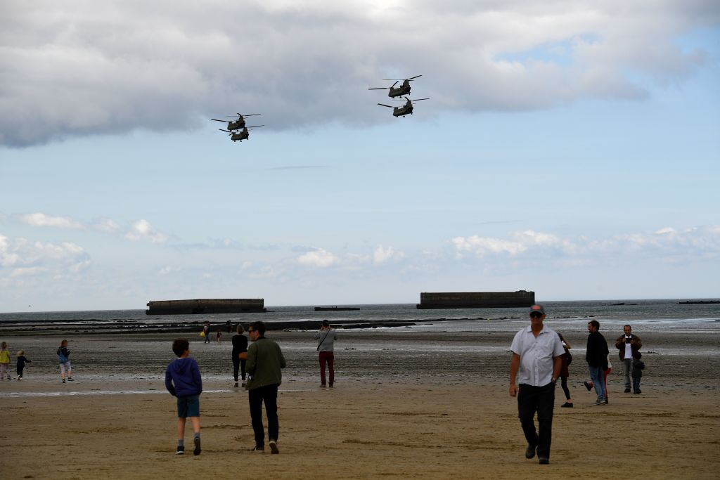 Visitors watch as CH-47 Chinook helicopters fly over the remains of Mulberry harbor, a temporary harbor built off the coast of Normandy by the British during World War II in 1944 in Arromanches-les-Bains, northwestern France on May 30,2019 during a rehearsal for DDAY commemorations. - The D-Day ceremonies on June 6, 2019, will mark the 75th anniversary since the launch of 'Operation Overlord', a vast military operation by Allied forces in Normandy, which turned the tide of World War II, eventually leading to the liberation of occupied France and the end of the war against Nazi Germany. (DAMIEN MEYER/AFP/Getty Images)