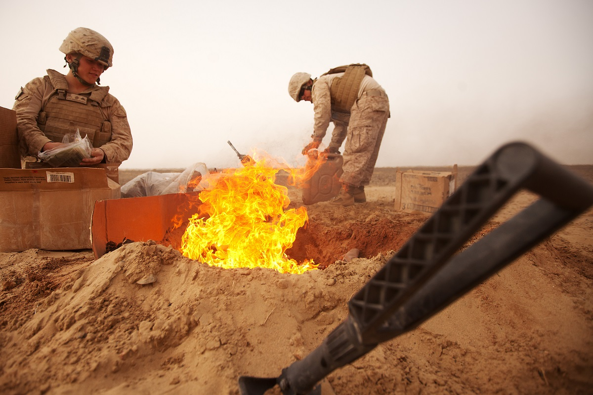 Marine Corps Lance Cpl. Nathanial Fink, left, and Lance Cpl. Garrett Camacho dispose of trash in a burn pit in the Khan Neshin district of Afghanistan in March 2012. (Cpl. Alfred V. Lopez/Marine Corps)