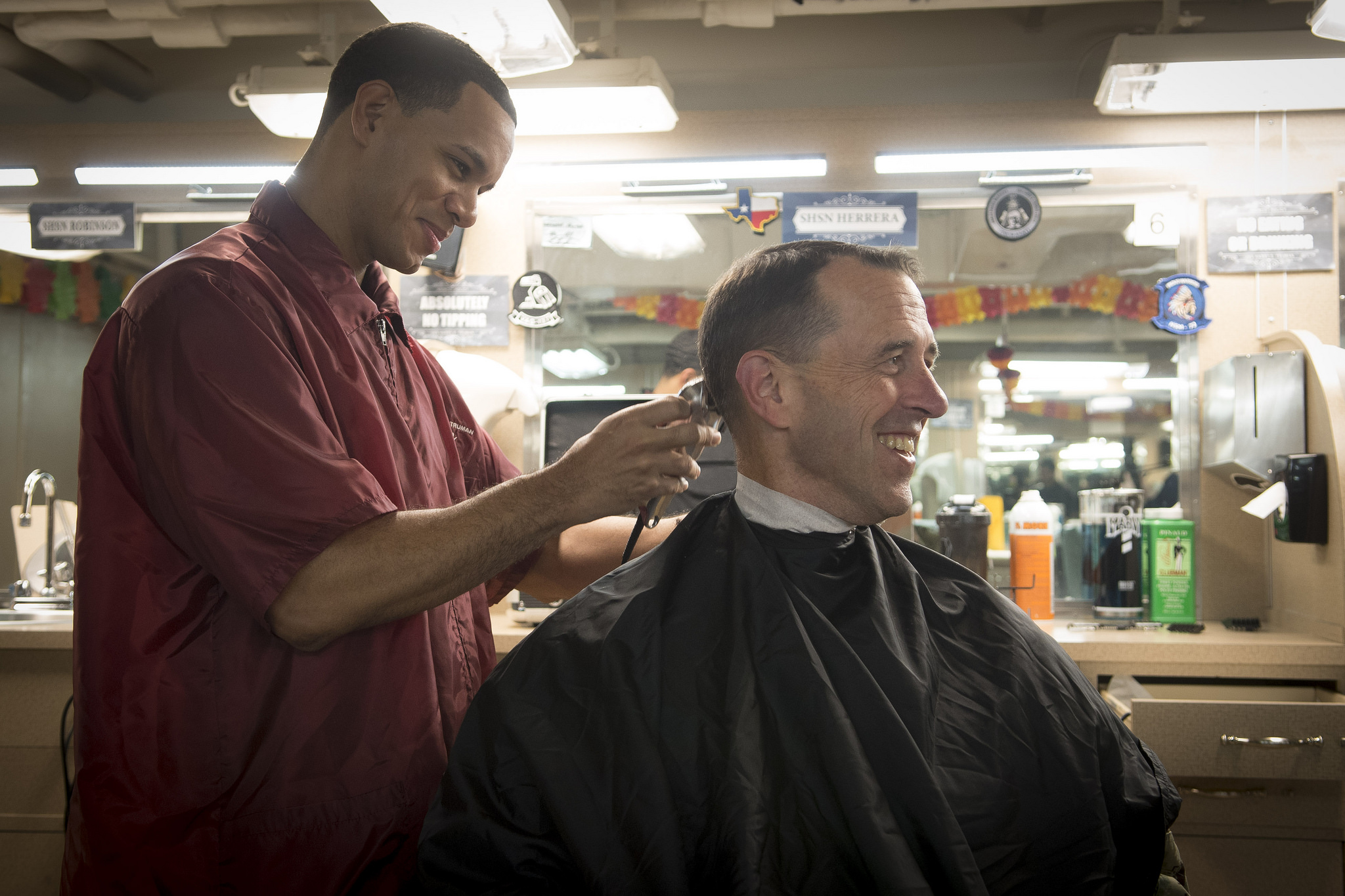 Ship's Serviceman 3rd Class Pedro Solis-Perez gives a haircut to Chief of Naval Operations Adm. John Richardson aboard the Nimitz-class aircraft carrier USS Harry S. Truman (CVN 75) on Nov. 23, 2018, in the Mediterranean Sea. Richardson and Master Chief Petty Officer of the Navy Russell Smith visited the ship to collect feedback and express their gratitude for the crew's warfighting readiness. (MC1 Sarah Villegas/Navy)