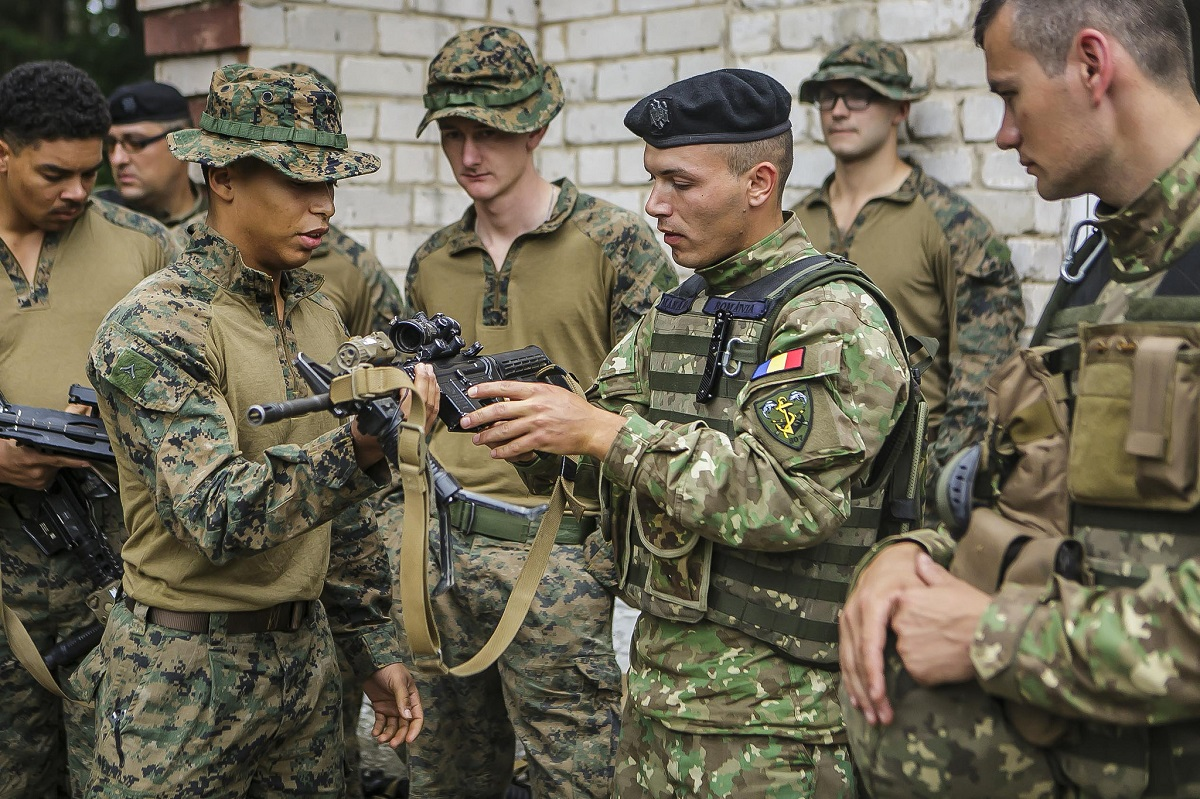 Keeping up foreign relations: A U.S. Marine shows off the M4A1 carbine rifle to Romanian marines taking part in a BALTOPS operation in Kairai, Lithuania, on June 4. (Dengrier M. Baez/U.S. Marine Corps)