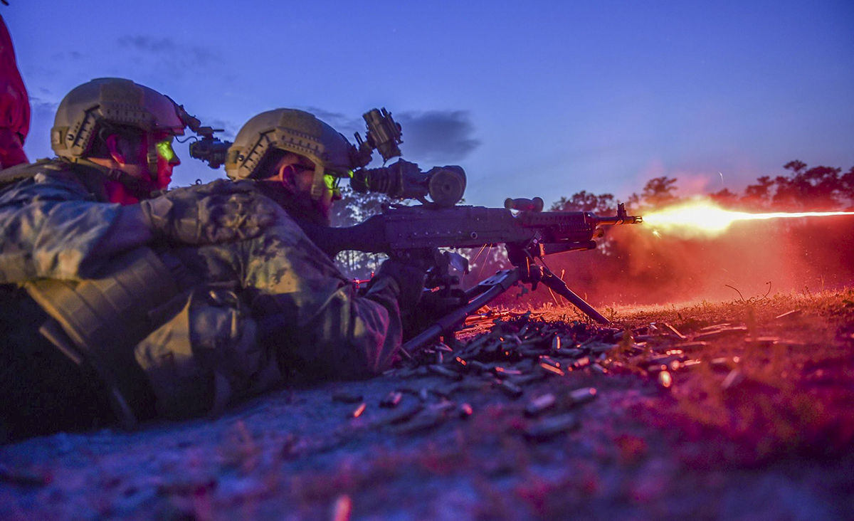 Marine Special Operations School Individual Training Course students fire an M249 squad automatic weapon during night-fire training April 13, 2017, at Camp Lejeune. For the first time, U.S. Air Force Special Tactics Airmen spent three months in Marine Special Operations Command's initial Marine Raider training pipeline, representing efforts to build joint mindsets across special operations forces. (Senior Airman Ryan Conroy/Air Force)