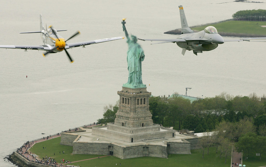An F-16 Viper and P-51 Mustang fly side by side near the Statue of Liberty in New York. (Courtesy of Victoria Arocho/Air Force)