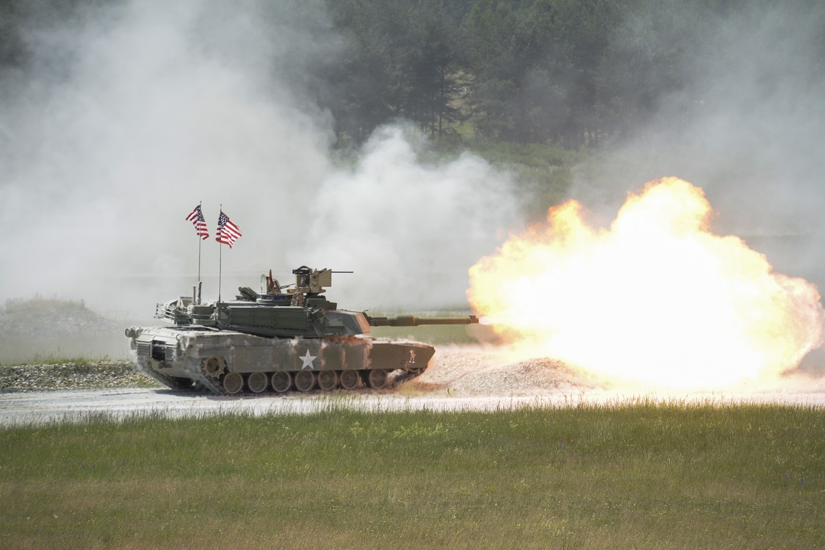 An M1A2 Abrams fires it's main gun during the Strong Europe Tank Challenge at Grafenwoehr Training Area, Germany, in June. The Army is converting another brigade combat team into an armored unit as it realigns the force to meet the challenge of a near-peer adversary. (Kevin S. Abel/Army)