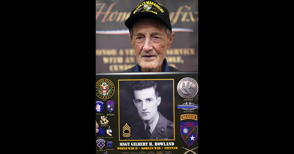 Gilbert Howland, of Langhorn, Pa., one of the few remaining members of the famed WWII Army unit Merrill's Marauders, poses for a portrait with a plaque bearing a photo of his younger self, during a gathering of remaining members, family and history buffs, in New Orleans, Tuesday, Aug. 28, 2018. (Gerald Herbert/AP)