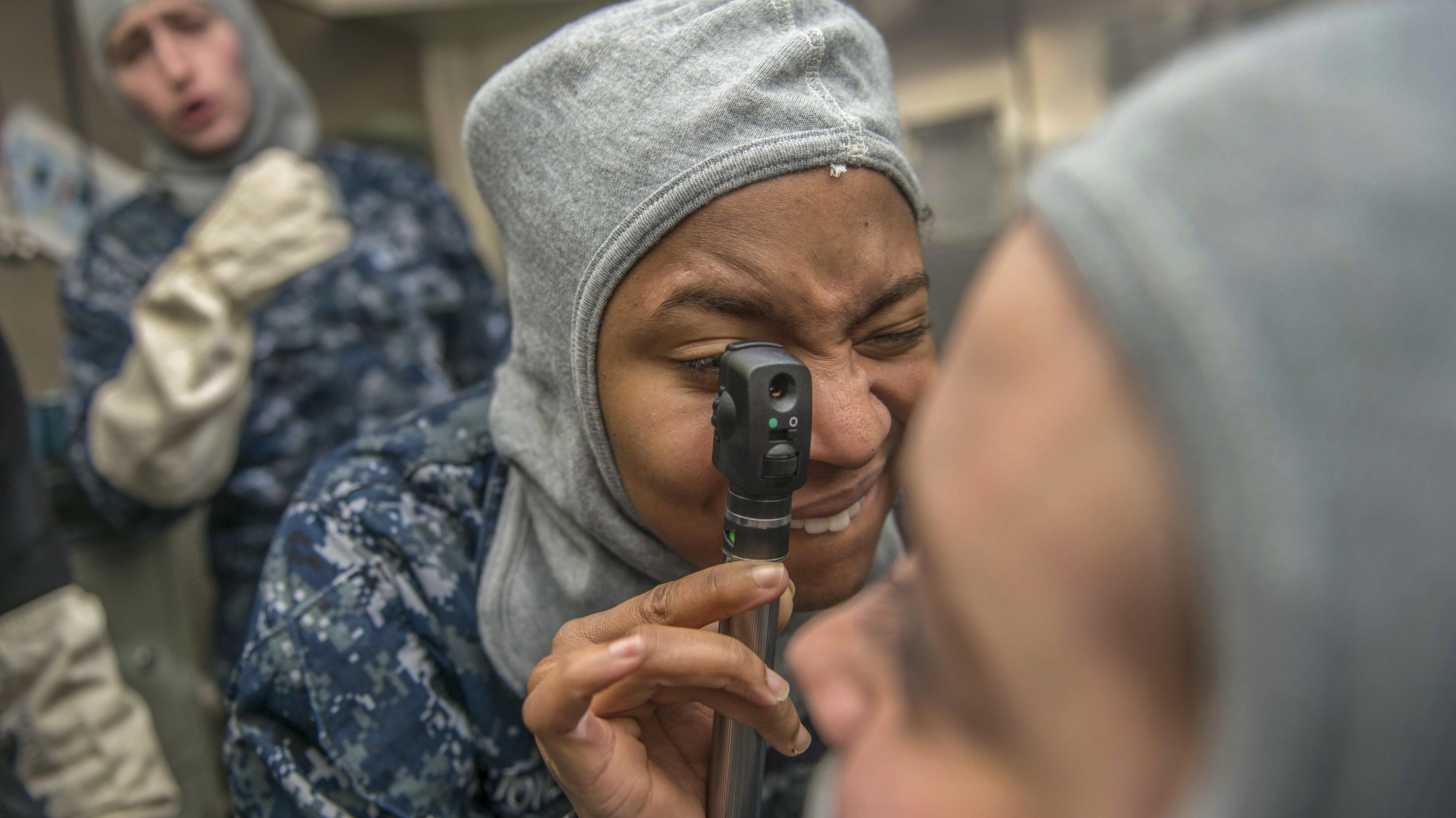 Navy Seaman Kiara Jones practices using an ophthalmoscope, a tool used to exam eyes, during a drill on the USS John C. Stennis in Bremerton, Wash., Nov. 29, 2017. The Stennis conducted routine training as it prepared for its next deployment. Navy photo by Jonathan Jiang