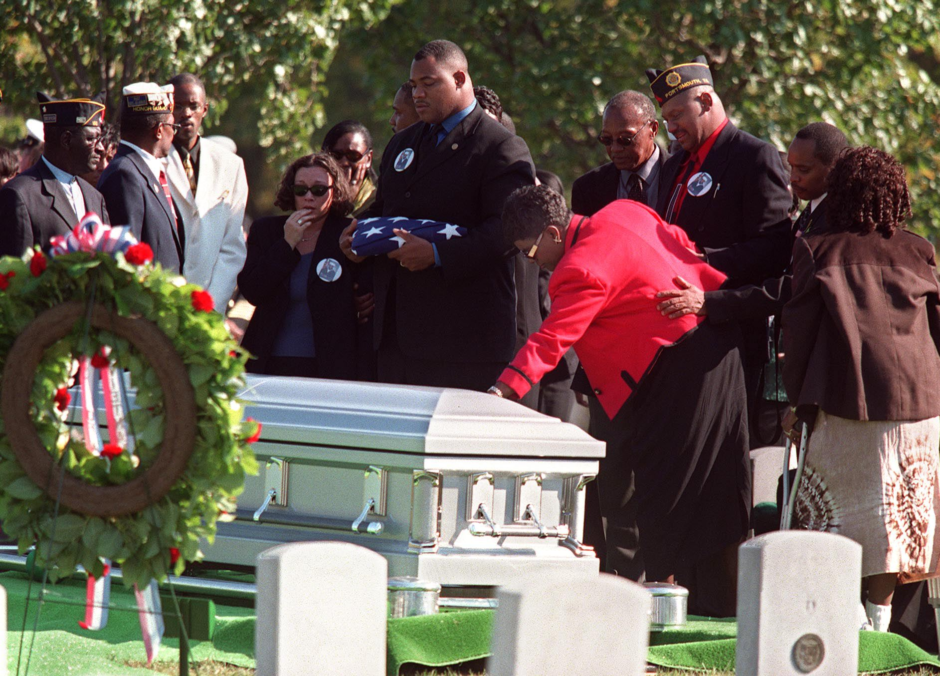 Mona Gunn (red jacket) touches the casket of her son, US Navy Signalman Seaman Apprentice Cherone Louis Gunn, as her husband Louge (3rd R) and son Anton (C) with family members look on 20 October 2000 during funeral services at Arlington National Cemetery in Virginia. Gunn was one of 17 US sailors killed in the suicide bombing attack of the USS Cole in the Yemeni port of Aden 12 October. (MANNY CENETA/AFP/Getty Images)