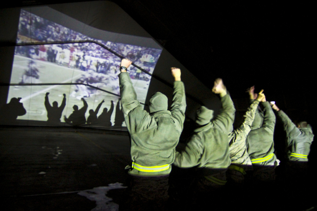New Jersey National Guard airmen watch Super Bowl XLVI projected onto the interior of an aircraft hangar in the early hours of Feb. 6, 2012, at Bagram Air Field, Afghanistan. (Tech. Sgt. Matt Hecht/Air Force)