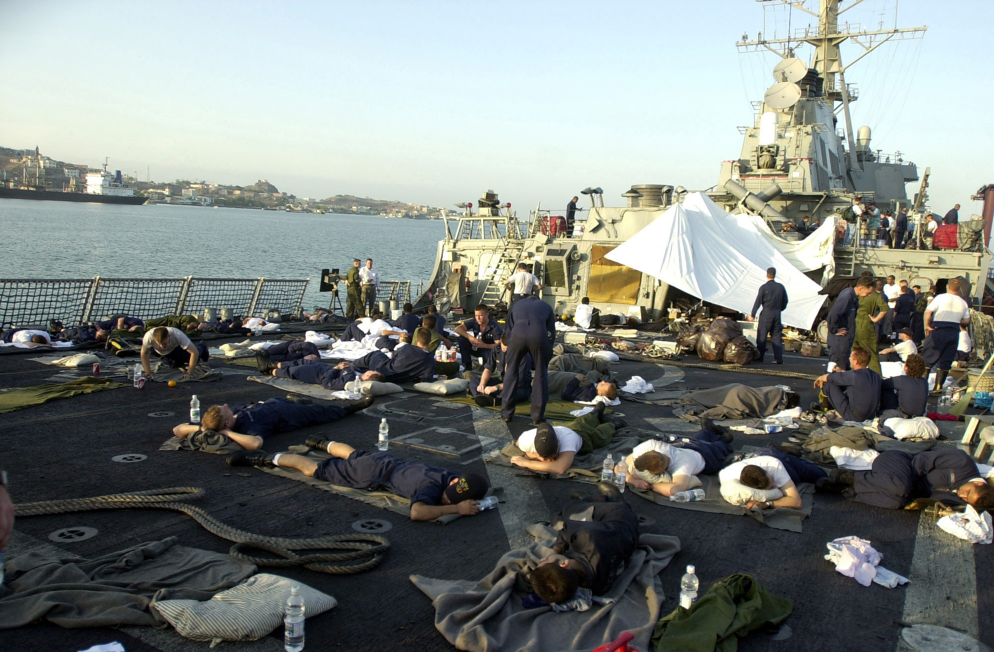 USS Cole sailors rest October 13, 2000 on the helicopter deck in Yemen following the October 12, 2000 terrorist bombing attack on their ship in the port of Aden, Yemen. (U.S. Navy Photo by Jim Watson)