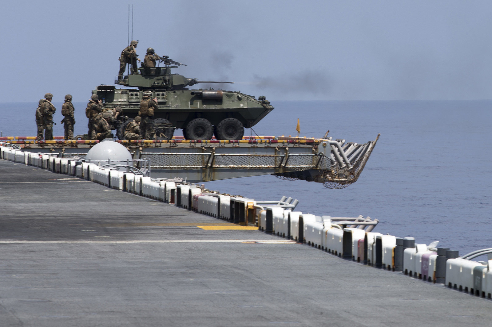 Marines with Weapons Company, Battalion Landing Team, 2nd Battalion, 5th Marines, sit on a Light Armored Vehicle atop the flight deck aboard the amphibious assault ship USS Wasp (LHD 1) on Sept. 27, 2018, during a defense of the amphibious task force drill in the South China Sea. During the training, Marines with BLT 2/5 and crewmen with the Wasp rehearsed ship security using a variety of mounted and dismounted small-arms and heavy weapons. (Gunnery Sgt. E. V. Hagewood/Marine Corps)