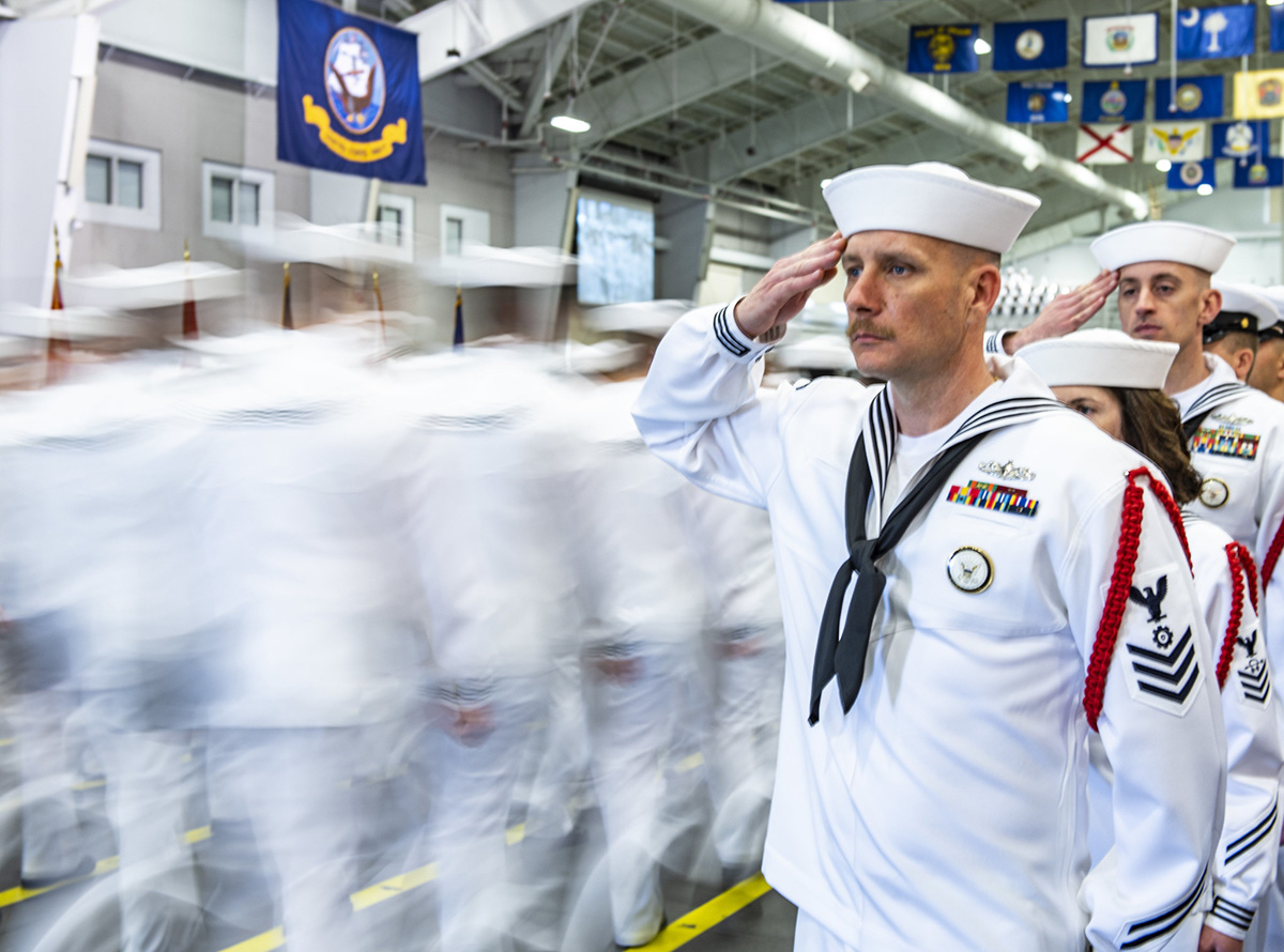 Recruit division commanders salute graduating divisions as they enter Midway Ceremonial Drill Hall on June 14, 2019, during a pass in review graduation ceremony at Recruit Training Command at Great Lakes, Ill. More than 35,000 recruits train annually at the Navy's only boot camp. (Mass Communication Specialist 1st Class Spencer Fling/Navy)