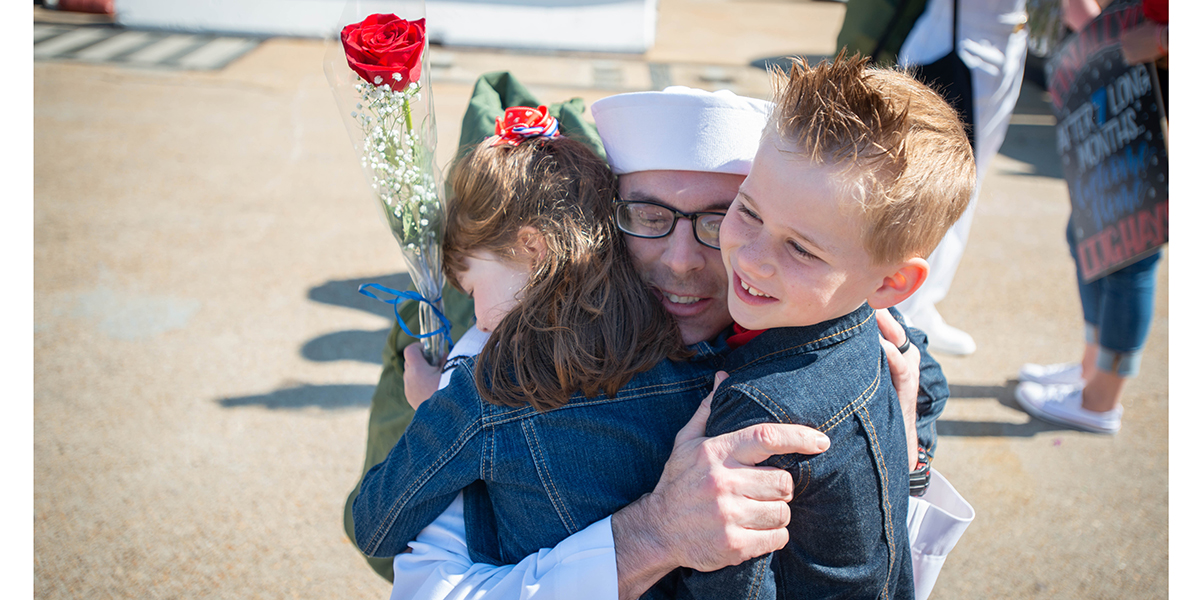 Master-at-Arms 1st Class Mitchell Huff hugs his children Keiran, 5, left, and Preston, 7, after disembarking the carrier John C. Stennis in Norfolk. (Mark D. Faram/Staff)