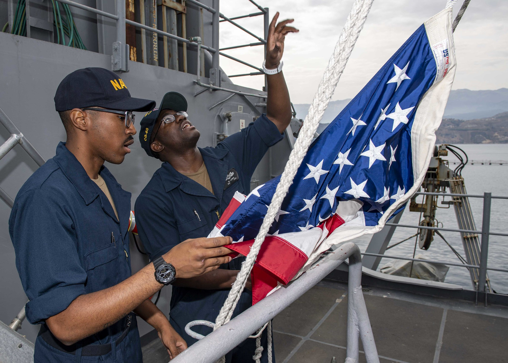 Quartermaster Seaman Marquis Lewis, right, instructs Quartermaster Seaman Khalil Hancock, on how to hoist the American flag as the Ticonderoga-class guided-missile cruiser USS Normandy (CG 60) prepares to depart Souda Bay, Greece, on Oct. 10, 2019. (Mass Communication Specialist 2nd Class Michael H. Lehman/Navy)