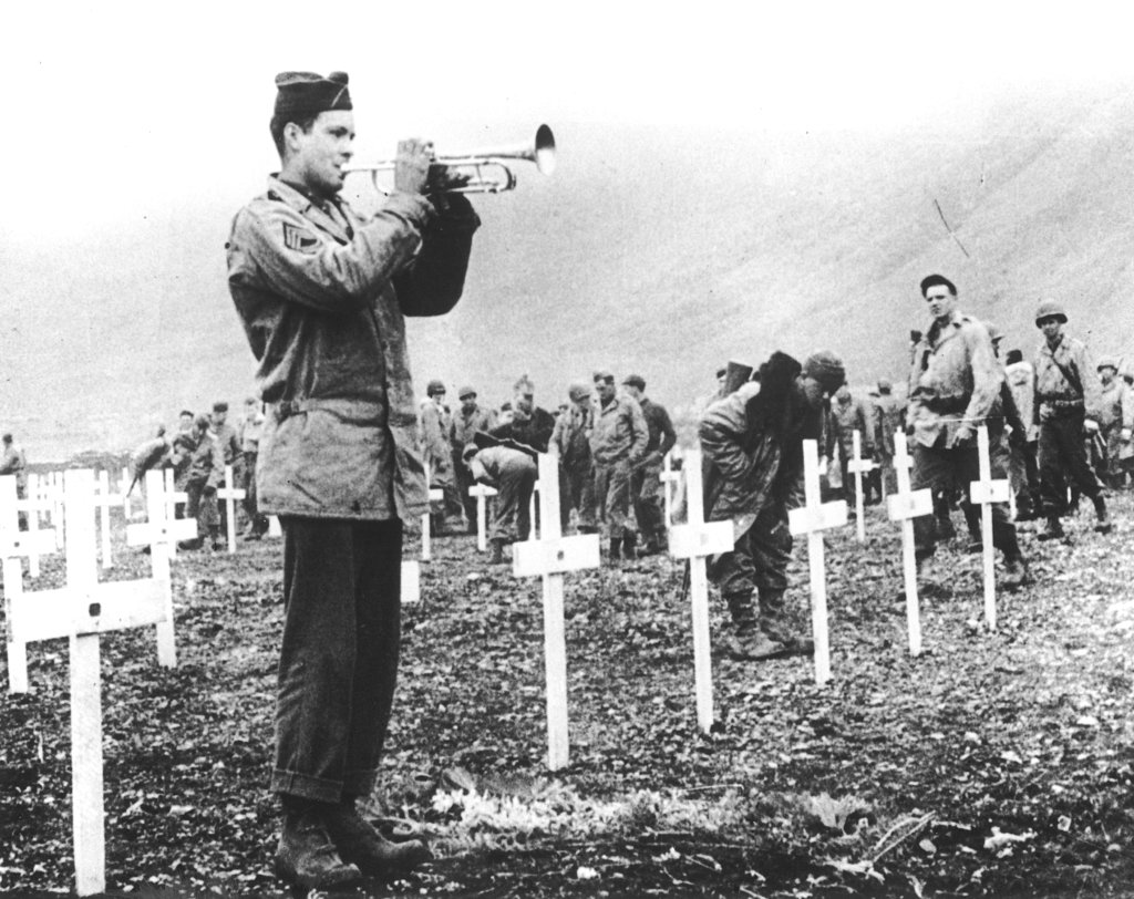 In this August 1943 file photo, a bugler sounds taps during a memorial service while a group of GIs visit the graves of comrades who fell in the reconquest of Attu Island, part of the Aleutian Islands of Alaska. May 30, 2018 will mark the 75th anniversary of American forces recapturing Attu Island in Alaska's Aleutian chain from Japanese forces. It was the only World War II battle fought on North American soil. (AP)