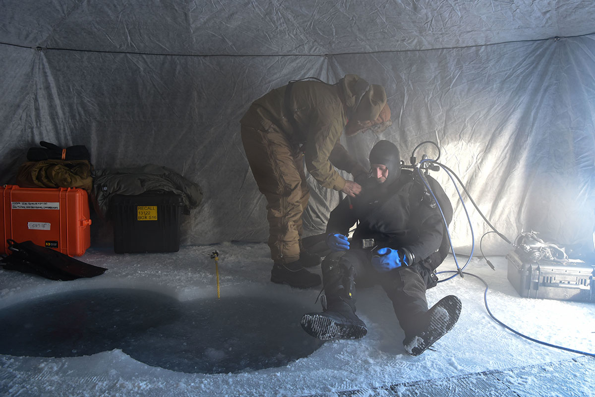 Ice Camp Skate (March 16, 2018) – Chief Hospital Corpsman Kristopher Mandaro, assigned to Underwater Construction Team One, prepares for a dive during a torpedo exercise in the Arctic Circle in support of ICEX 2018.(photo by MC1 Daniel Hinton/Navy)