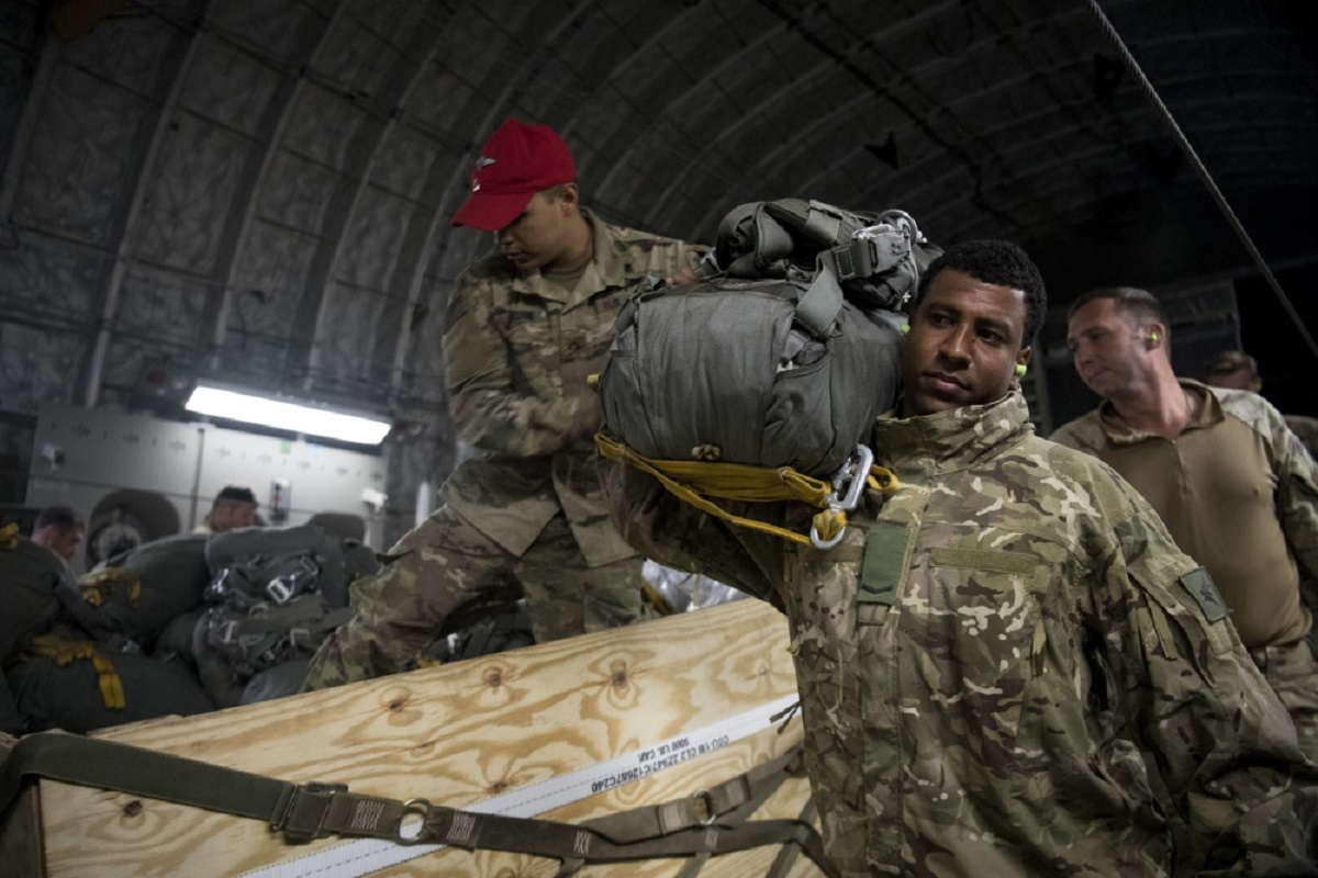 U.S. Army paratroopers assigned to the 82nd Airborne Division on Fort Bragg, N.C., and British Army paratroopers assigned to the 3rd Regiment Parachute Battalion out of Colchester, England, rig their parachutes in preparation for a jump from a C-17 Globemaster III over Latvia during Exercise Swift Response 18 on June 8. (U.S. Air Force)
