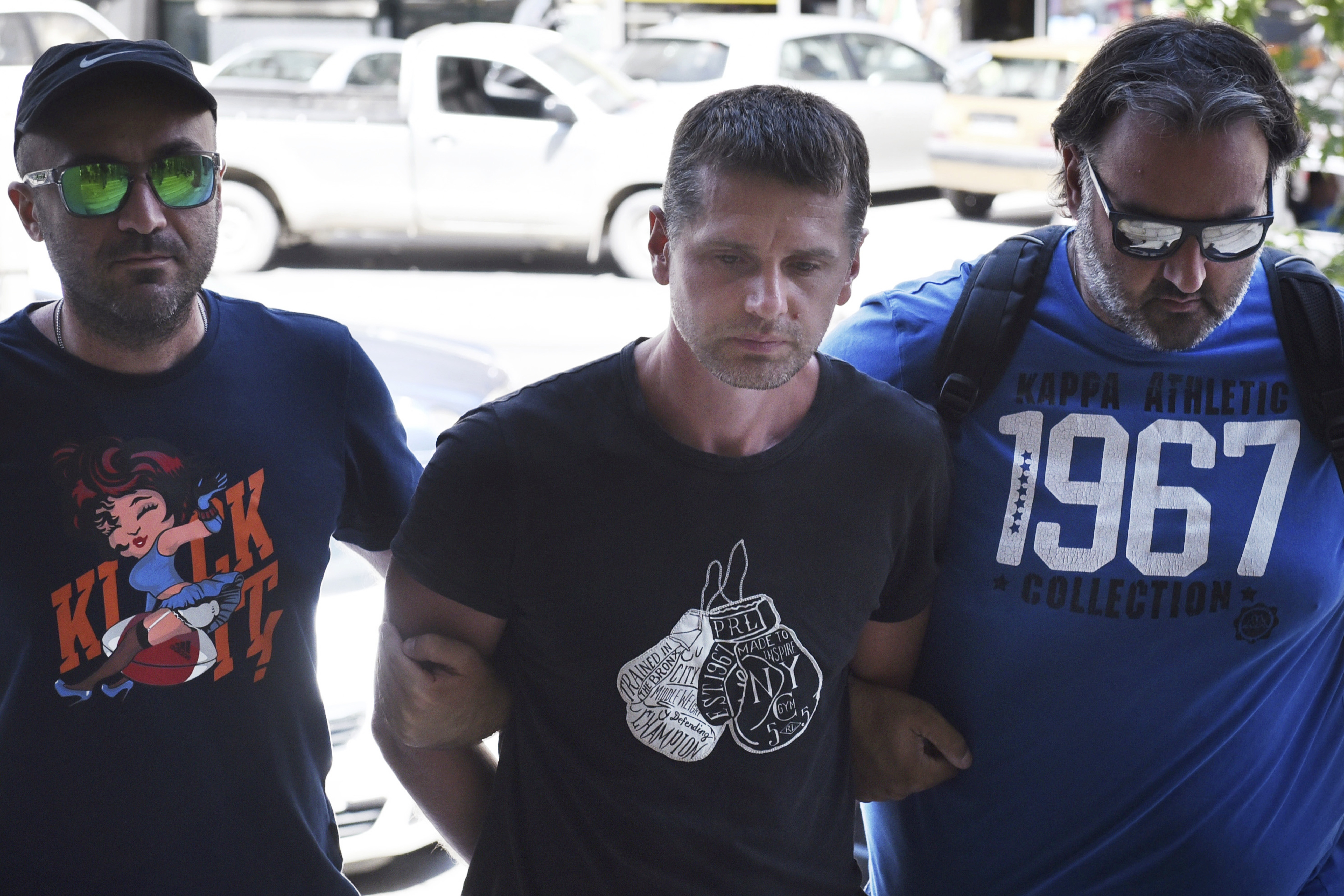 In this Wednesday, July 26, 2017 file photo a Russian man identified as Alexander Vinnik, center, is escorted by police officers to the courthouse at the northern Greek city of Thessaloniki. Vinnik's lawyer, Xanthippe Moyssidou, told The Associated Press on Tuesday Sept. 19, 2017, that Vinnik was also wanted in Russia on separate fraud charges. He says he has told Greek authorities he would not challenge the request to extradite Vinnik to Russia. (Giannis Papanikos/AP)
