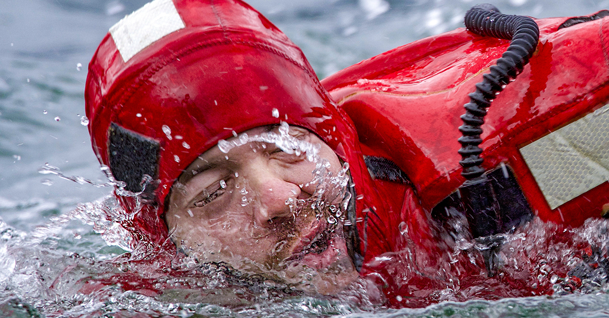 A Coast Guard members face emerges from the frigid water while competing in the survival swim relay during the Buoy Tender Roundup Olympics in Juneau, Alaska, Aug. 22, 2018. Crews aboard Coast Guard buoy tenders in Alaska service 1,350 navigational aids along 33,000 miles of coastline while actively participating in search and rescue, environmental protection and law enforcement missions. (Petty Officer 1st Class Jon-Paul Rios/Coast Guard)