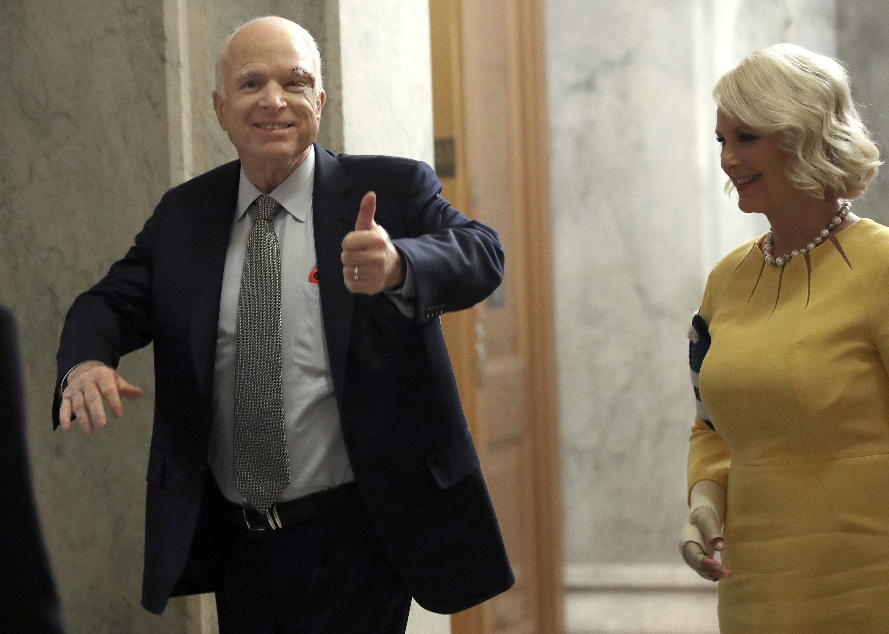 Sen. John McCain, R-Ariz., left, returns to the U.S. Senate accompanied by his wife Cindy on July 25, 2017, in Washington. McCain was recently diagnosed with brain cancer but returned on the day the Senate is holding a key procedural vote on President Donald Trump's effort to repeal and replace the Affordable Care Act. (Win McNamee/Getty Images)