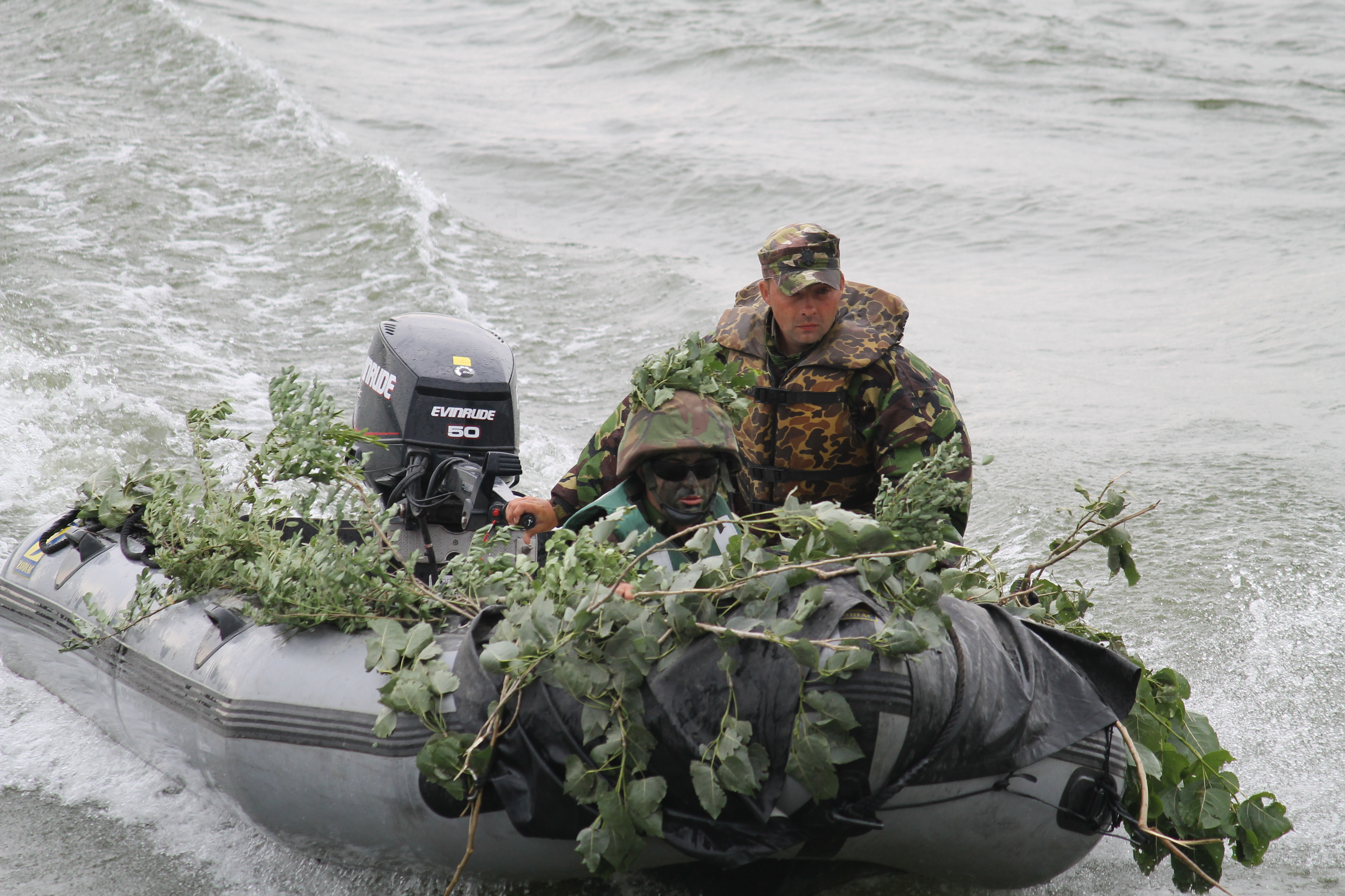 A camouflaged raft zips across the Danube, picking up more troops to carry back. The process of moving units across the river several times took just a few minutes. (Jen Judson/Staff)
