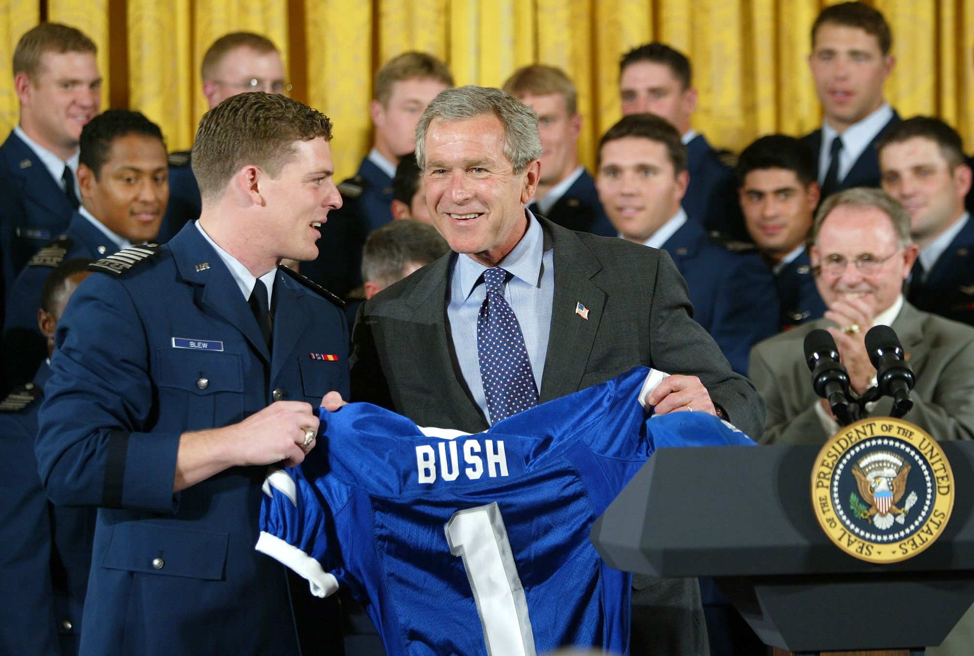 Air Force Academy football team wide receiver Bryan Blew gives President Bush a Falcon jersey during a visit to the East Room of the White House, Friday, May 16, 2003. It is the sixth straight year the Air Force Academy, in Colorado Springs, Colo., has won the commander in chief's trophy which is awarded to the military service academy with the best record against the other two service academies. Head Football Coach Fisher DeBerry applauds at right. (AP Photo/J. Scott Applewhite)