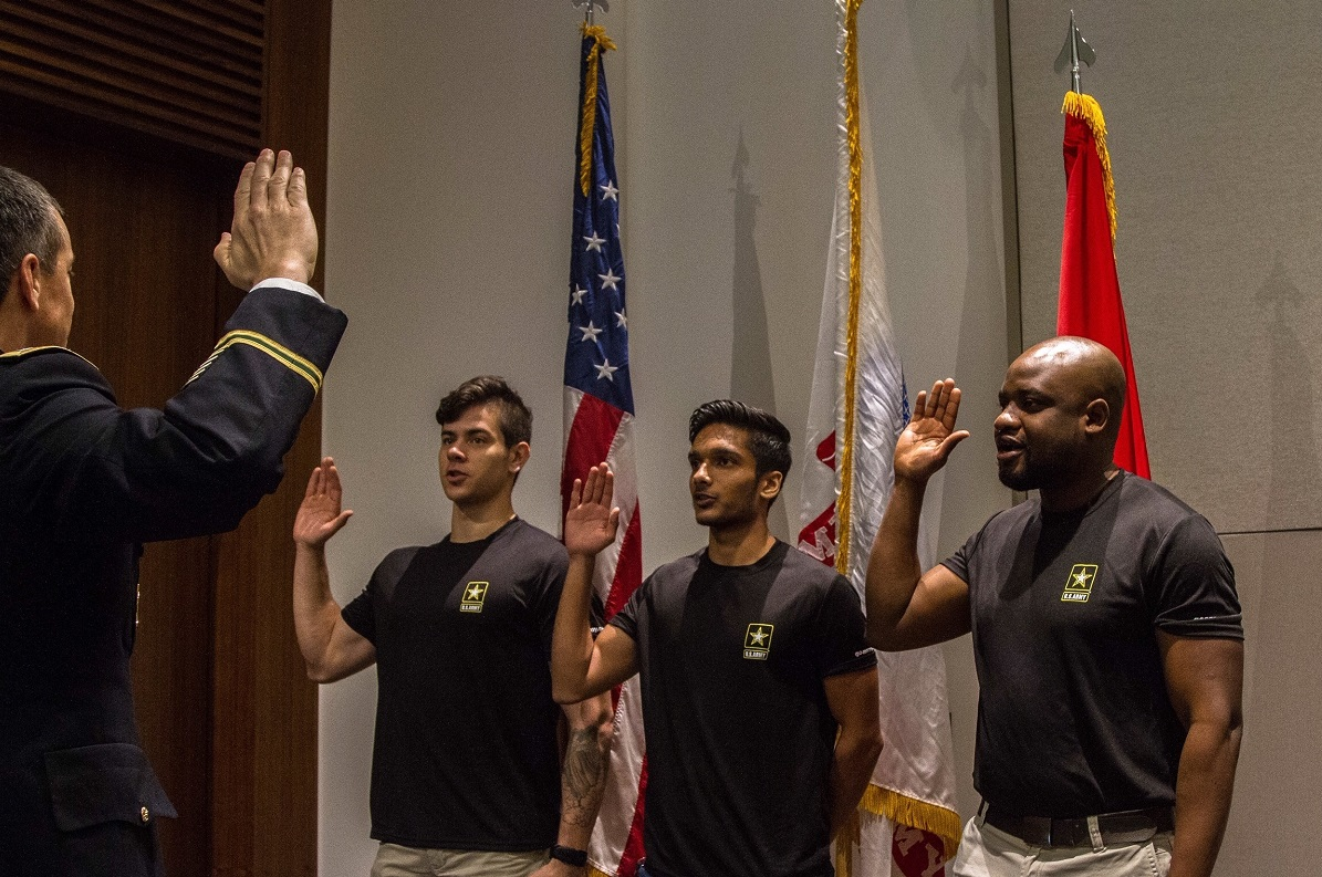 The commander of the Houston Recruiting Battalion performs an enlistment ceremony for Houston residents Pvt. Vincent Digiacomo, Pfc. Kirtan Patel and Nigerian born and current Houston resident Pvt. Ayoola Oyewale Feb. 27 at Halliburton's headquarters in Houston. (Army Sgt. 1st Class Kelvin Ringold/Marine Corps)