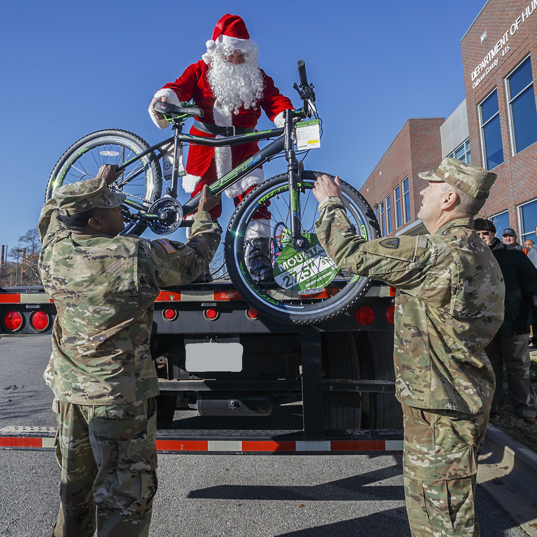 Santa hands a bike to Anniston Army Depot Sgt. Maj. Ronald Ferdinand and Tank, Automotive and Armaments Command Chaplain Lt. Col. David Snyder at the Calhoun County Department of Human Resources. The depot's 2017 Christmas Cheer program culminated Dec. 10, 2017, with the delivery of three truckloads of gifts and bicycles to the DHR office in Anniston. (Jeffrey Cleghorn/Army)