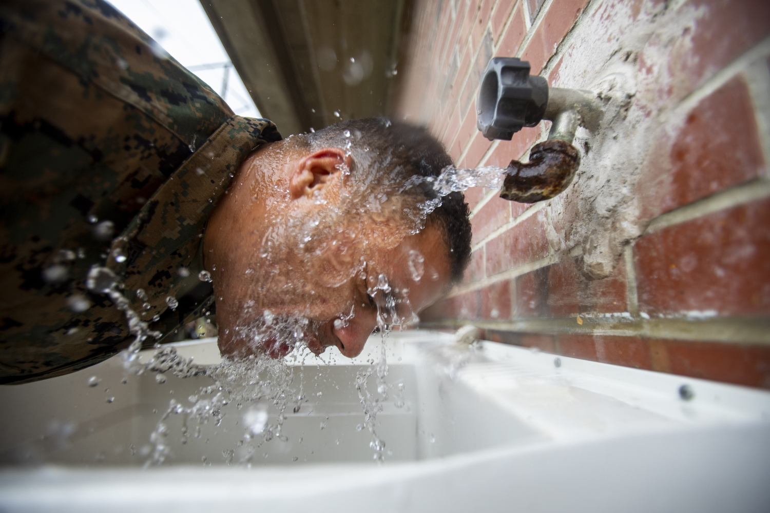 A Marine attached to Deployment Processing Command Reserve Support Unit-East, Force Headquarters Group, runs water on his face after gas chamber training at Marine Corps Base Camp Lejeune, N.C., Oct. 22, 2019. (Sgt. Andy O. Martinez/Marine Corps)