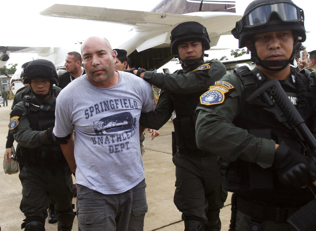 In this Sept. 26, 2013, file photo, Joseph Hunter, second from left, a former U.S. Army sniper who became a private mercenary, is in the custody of Thai police commandos after being arrested in Bangkok, Thailand. Hunter and two other ex-American soldiers were convicted Wednesday in the contract killing of a real estate agent in the Philippines for an international crime boss who thought the woman had cheated him on a land deal. (Sakchai Lalit/AP)