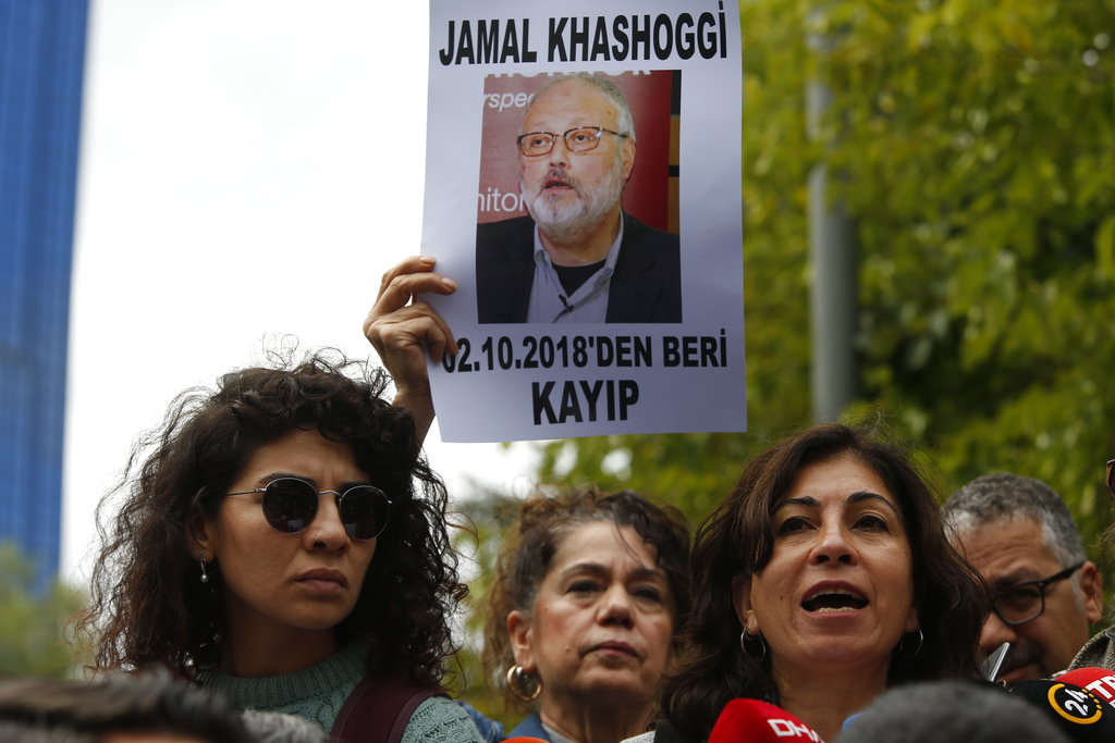 Activists hold posters with photos of Saudi journalist Jamal Khashoggi. (Lefteris Pitarakis/AP)