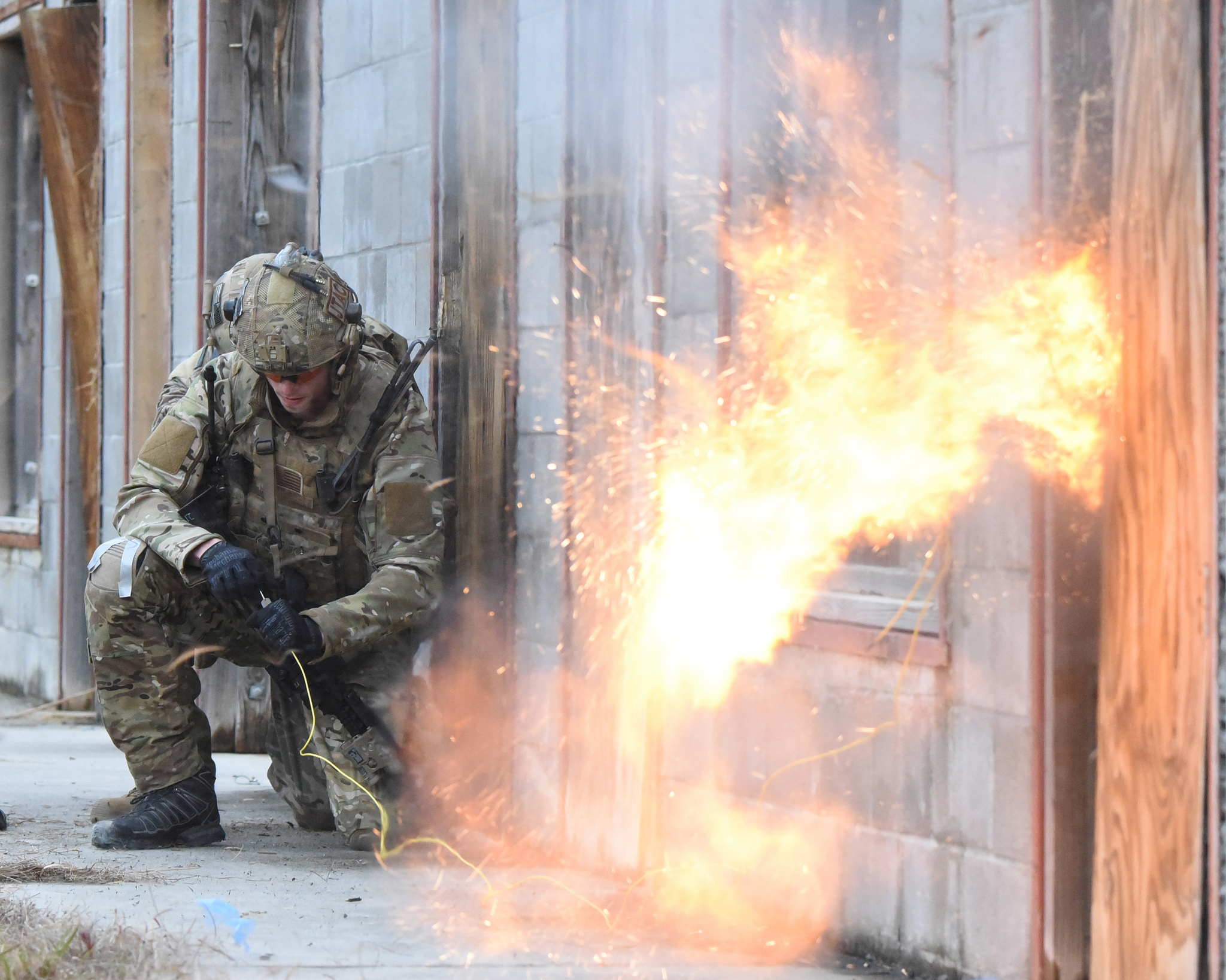 A tactical air control party airman detonates an explosive tool mounted on a door as an explosives ordnance technician provides support as they prepare to breach a door during exercise Southern Strike 19 at Camp Shelby Joint Forces Training Center near Hattiesburg, Miss., Jan. 18, 2019. (Chief Master Sgt. David H. Lipp/Air National Guard)