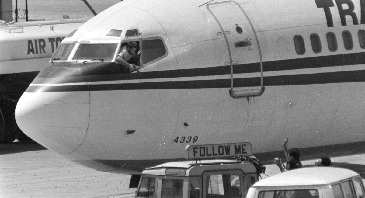 In this June 19, 1985 photo, a hijacker points a weapon toward an ABC news media crew from the window of the cockpit of the Trans World Airlines jet at Beirut International Airport. (Herve Merliac/AP)