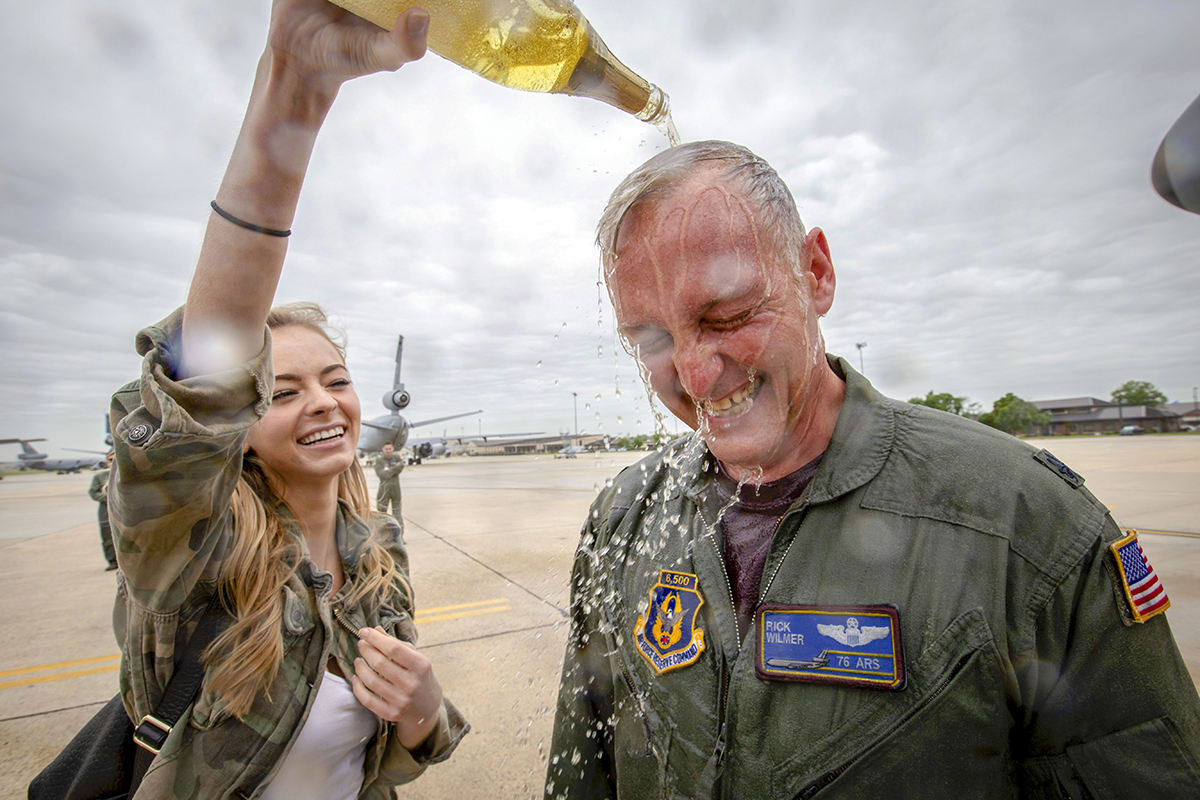 U.S. Air Force Lt. Col. Frederick M. Wilmer III, a KC-10 Extender pilot with the 76th Air Refueling Squadron, 514th Air Mobility Wing, has apple cider poured on him by his daughter, Samantha, after completing his final flight at Joint Base McGuire-Dix-Lakehurst, N.J., May 18, 2018. The final flight, or fini-flight, is a tradition among pilots and air crew to celebrate one's last flight with their unit or on a certain airframe. The 514th is an Air Force Reserve Command unit. (Master Sgt. Mark C. Olsen/Air Force)