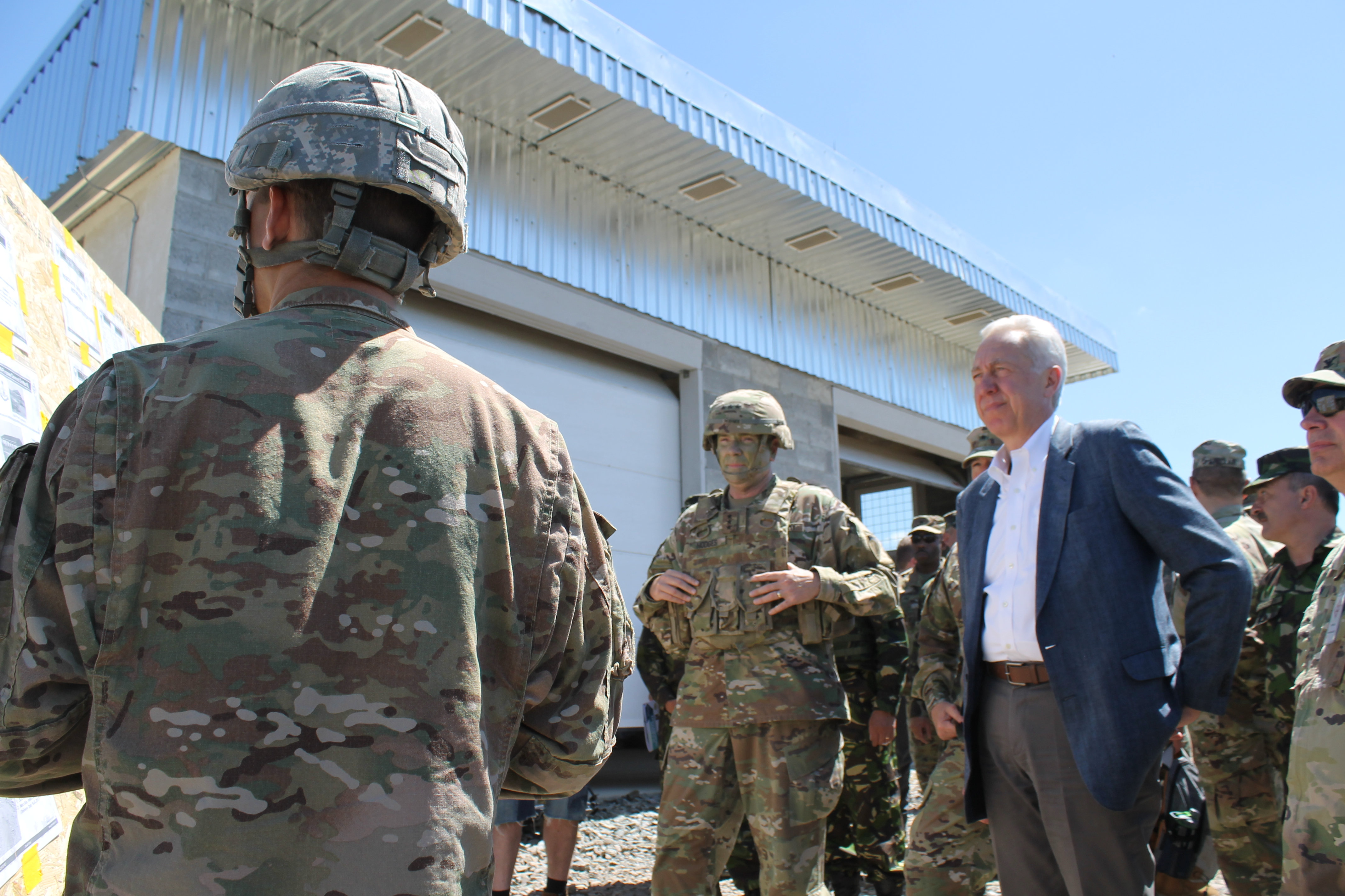 Lt. Gen. Ben Hodges and U.S. ambassador to Romania Hans Klemm listen to a briefing from a soldier from the 926th Engineer Brigade on the work the unit, comprised of National Guard and Reserve forces as well as British and Romanian soldiers, has been doing to build up the Joint National Training Center in Cincu, Romania, to include ammunition storage, a nonstandard live fire course for tanks with moving armored targets, a light demolition range and a sniper range. (Jen Judson/Staff)