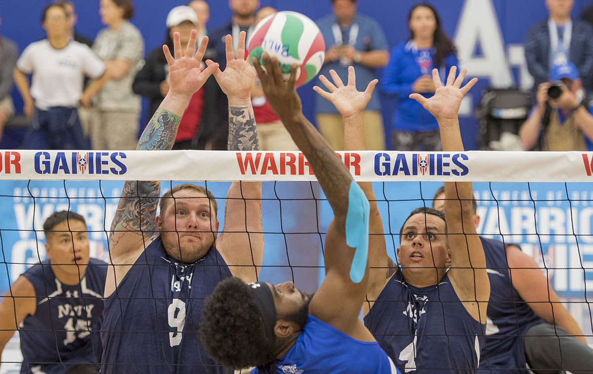 Air Force veteran Staff Sgt. Anthony Pearson tries to push the ball past Navy Petty Office 1st Class Tyson Schmidt, left, and veteran Chief Petty Office Javier Santiago during sitting volleyball preliminaries at the 2018 DoD Warrior Games at the U.S. Air Force Academy in Colorado Springs on June 3, 2018. The Warrior Games are an annual event, established in 2010, to introduce wounded, ill and injured service members to adaptive sports as a way to enhance their recovery and rehabilitation. (Roger L. Wollenberg/DoD)