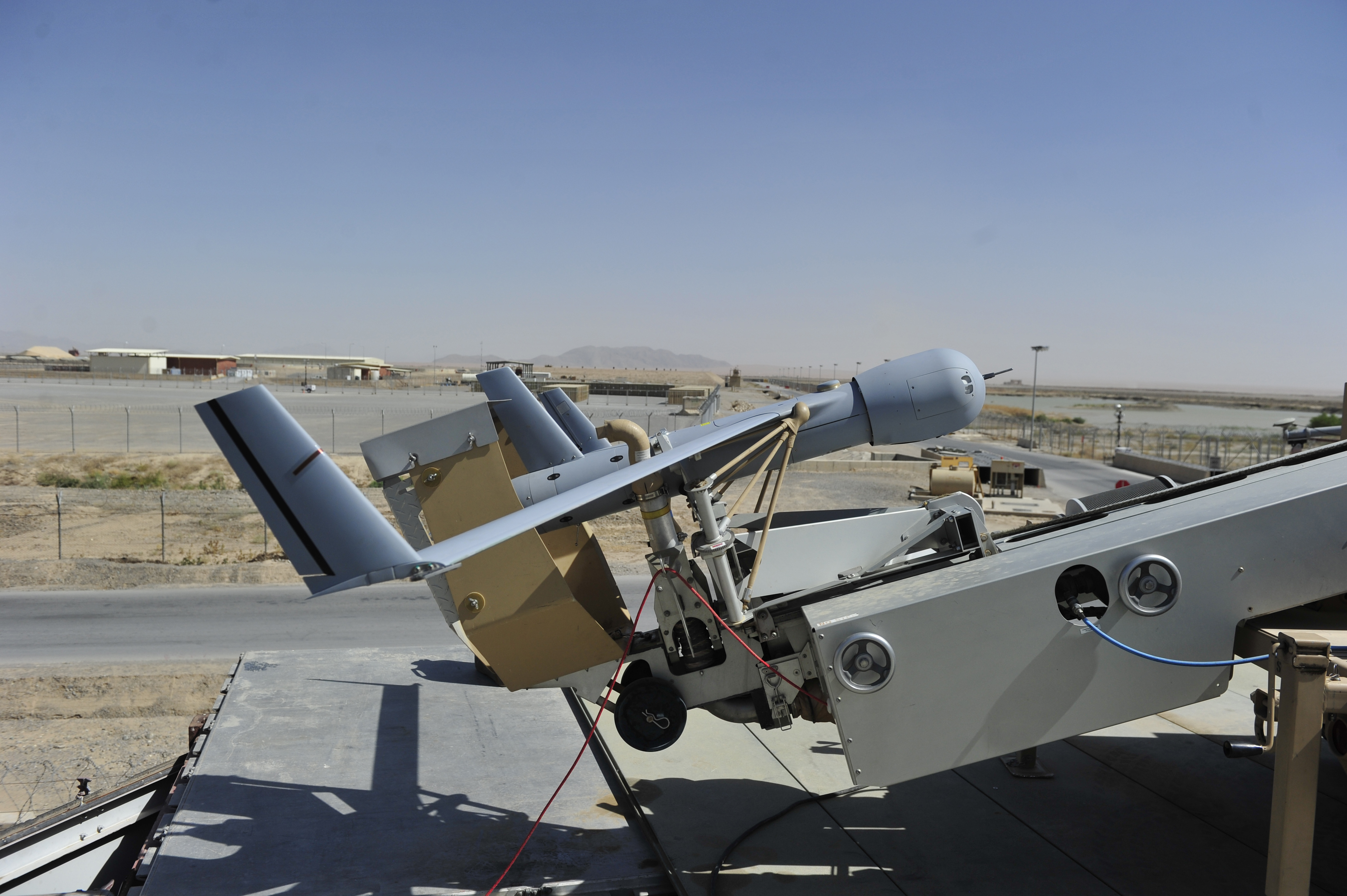 A ScanEagle unmanned aerial vehicle sits ready for launch by Rear Adm. Luke McCollum, vice commander, U.S. Naval Forces Central Command, at Kandahar Airfield. (Lt. Kristine Volk, Resolute Support Public Affairs/U.S. Navy)