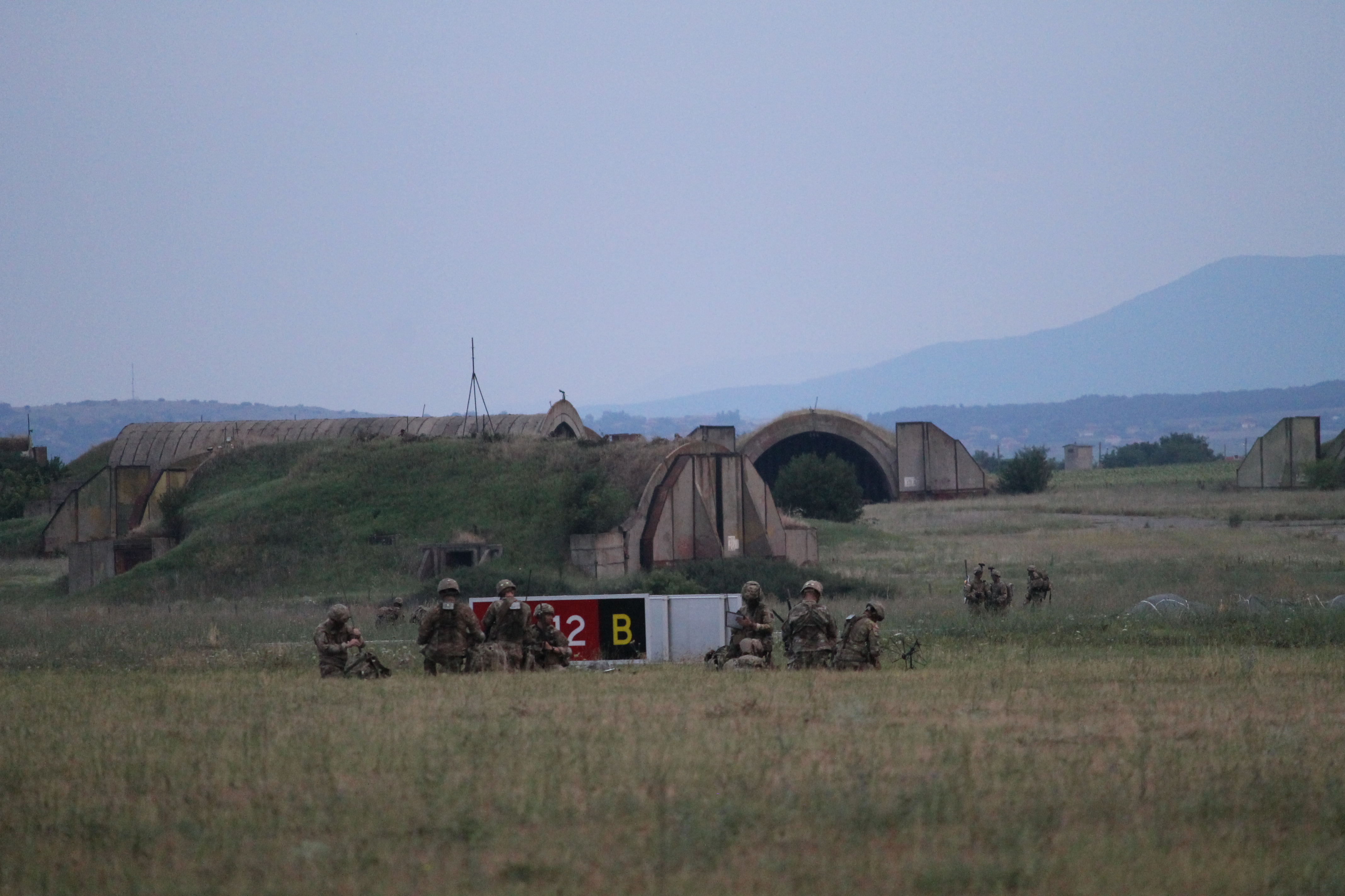 Paratroopers collect on the ground at the perimeter of a series of airplane hangars that collectively look like a hobbit shire. The opposition forces, played by Bulgarian soldiers, sporadically fired at the paratroopers. In a real operation, paratroopers would not land directly in front of the enemy, but for the purposes of observing, everything is designed to happen in close proximity. (Jen Judson/Staff)