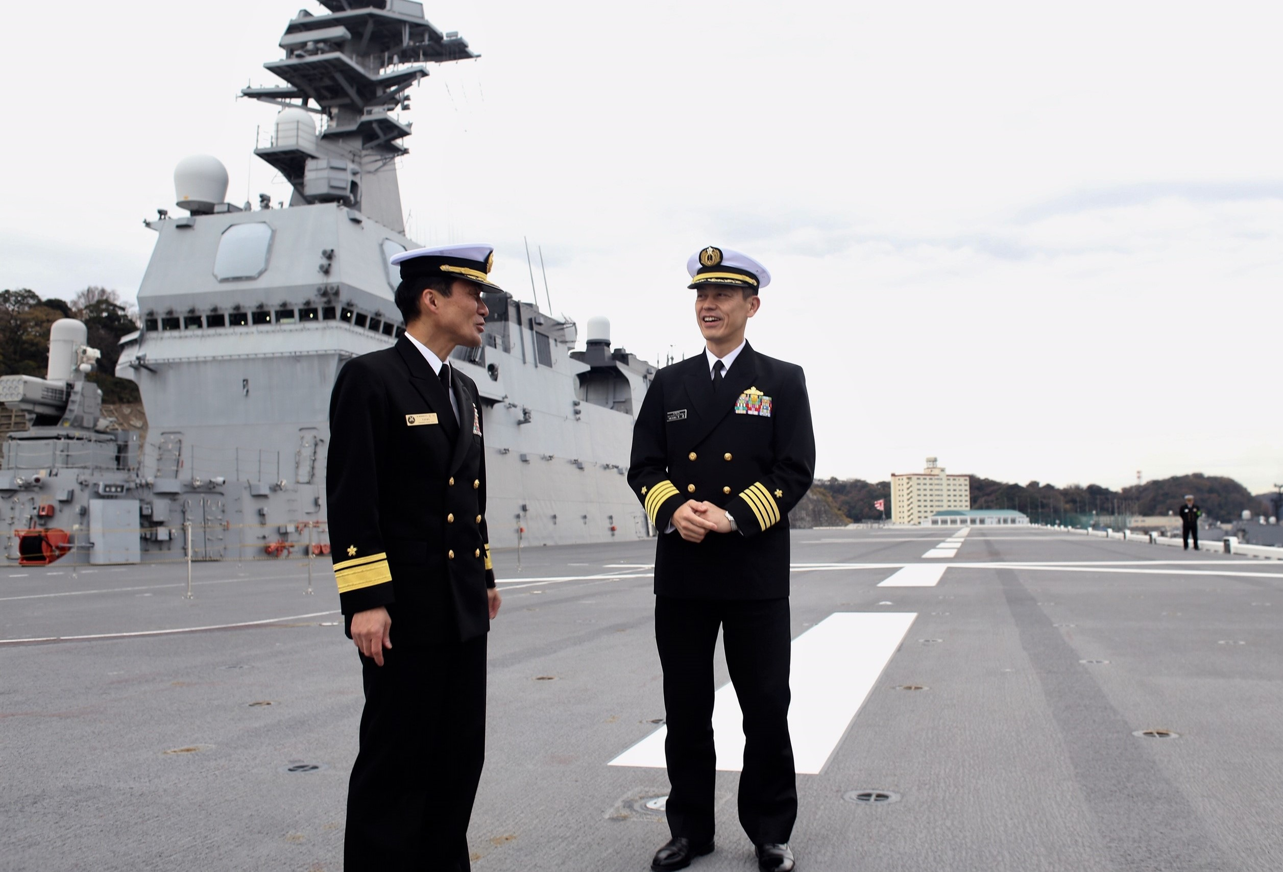 Japanese Maritime Self Defense Forces Capt. Katsuyoshi Motoyama, left, commanding officer of the JS Izumo, and Capt.Toshiyuki Hirata, deputy director of plans and programs, stand on the Izumo's flight deck in port at Naval Base Yokosuka in December. Japan is planning to convert the Izumo into an aircraft carrier and outfit it with F-35s in response to China's rapid military expansion. (Tara Copp/Military Times)