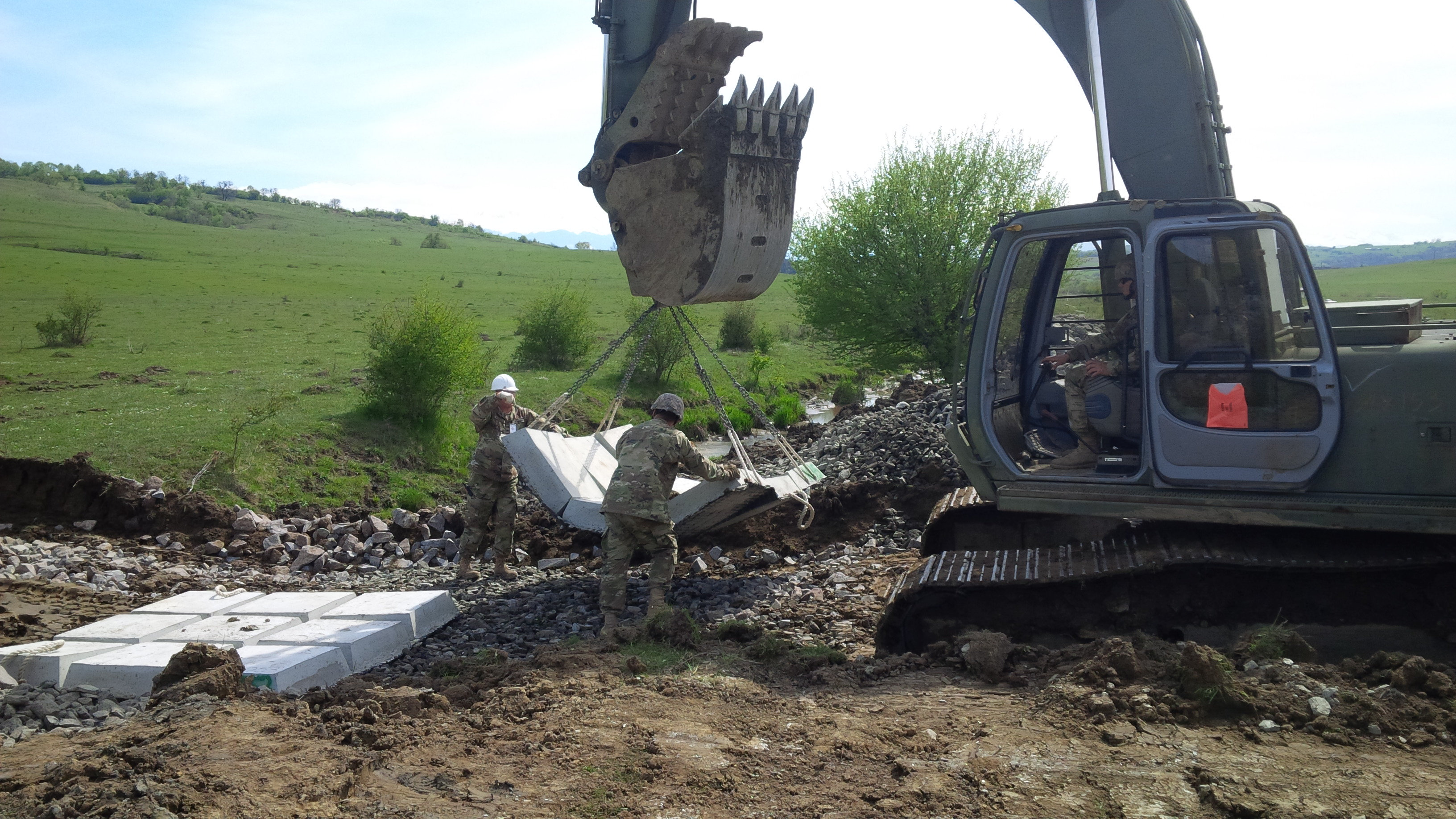 An excavator is used to place concrete mattresses on a low-water crossing being built for the Romanians so their field artillery can reach an area for setup. (Jen Judson/Staff)