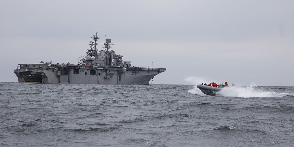 A rigid hull inflatable boat passes in front of the amphibious assault ship Bataan while the amphib completed sea trials following a long overhaul session. (Mass Communication Specialist 2nd Class Zachary A. Anderson/Navy)