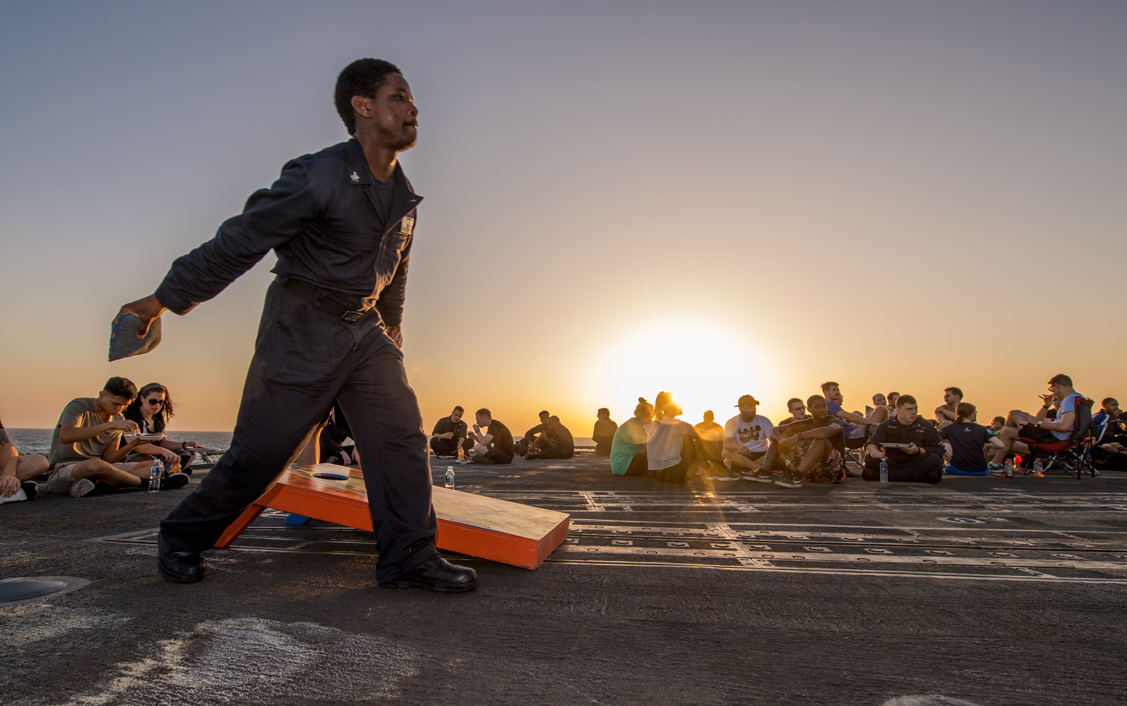 Information Systems Technician 2nd Class Philmore Daley, from Lemoore, Calif., plays cornhole during a steel beach picnic on the flight deck of the Ticonderoga-class guided-missile cruiser USS Princeton (CG 59), Oct. 15, 2017. (Mass Communication Specialist 3rd Class Kelsey J. Hockenberger/Navy)