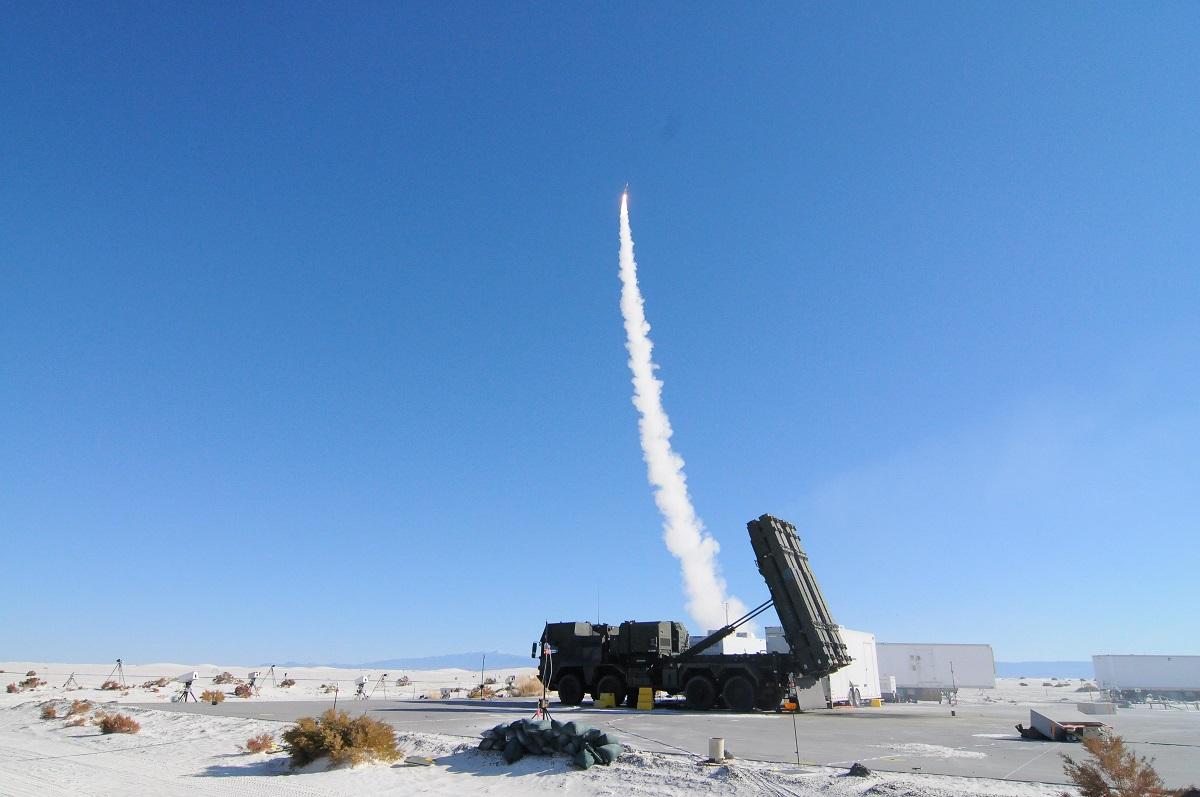 A MEADS launcher sits ready while a second fires a missile in the background at White Sands Missile Range, New Mexico, in 2013. (White Sands Missile Range Public Affairs)