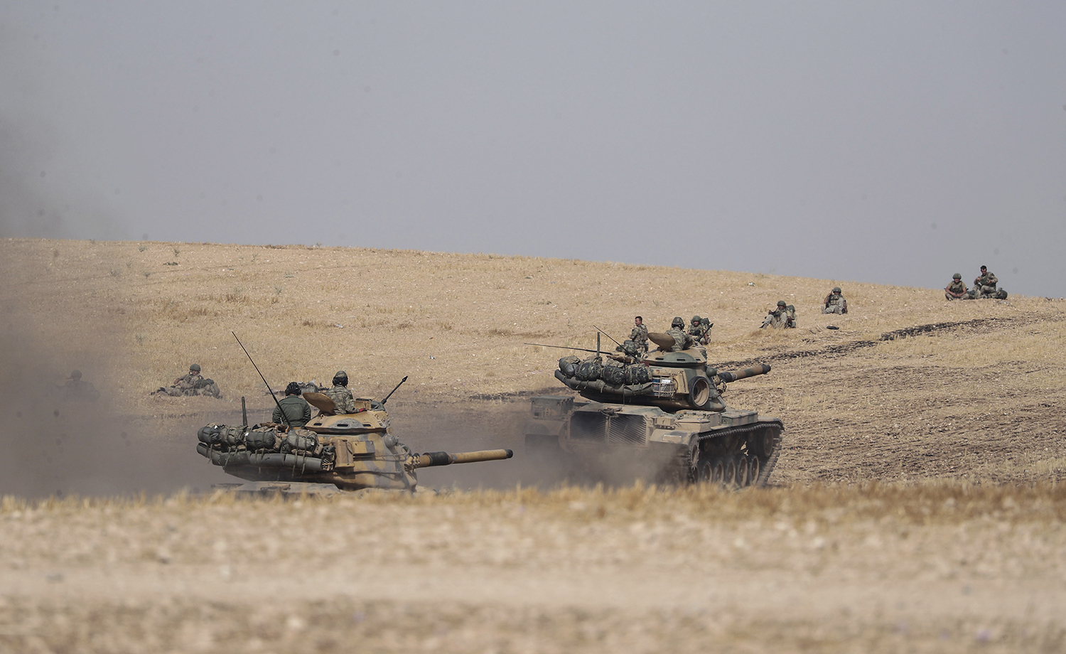 Turkish tanks and troops stationed near Syrian town of Manbij, Syria, Tuesday. Oct. 15, 2019. (Ugur Can/DHA via AP)